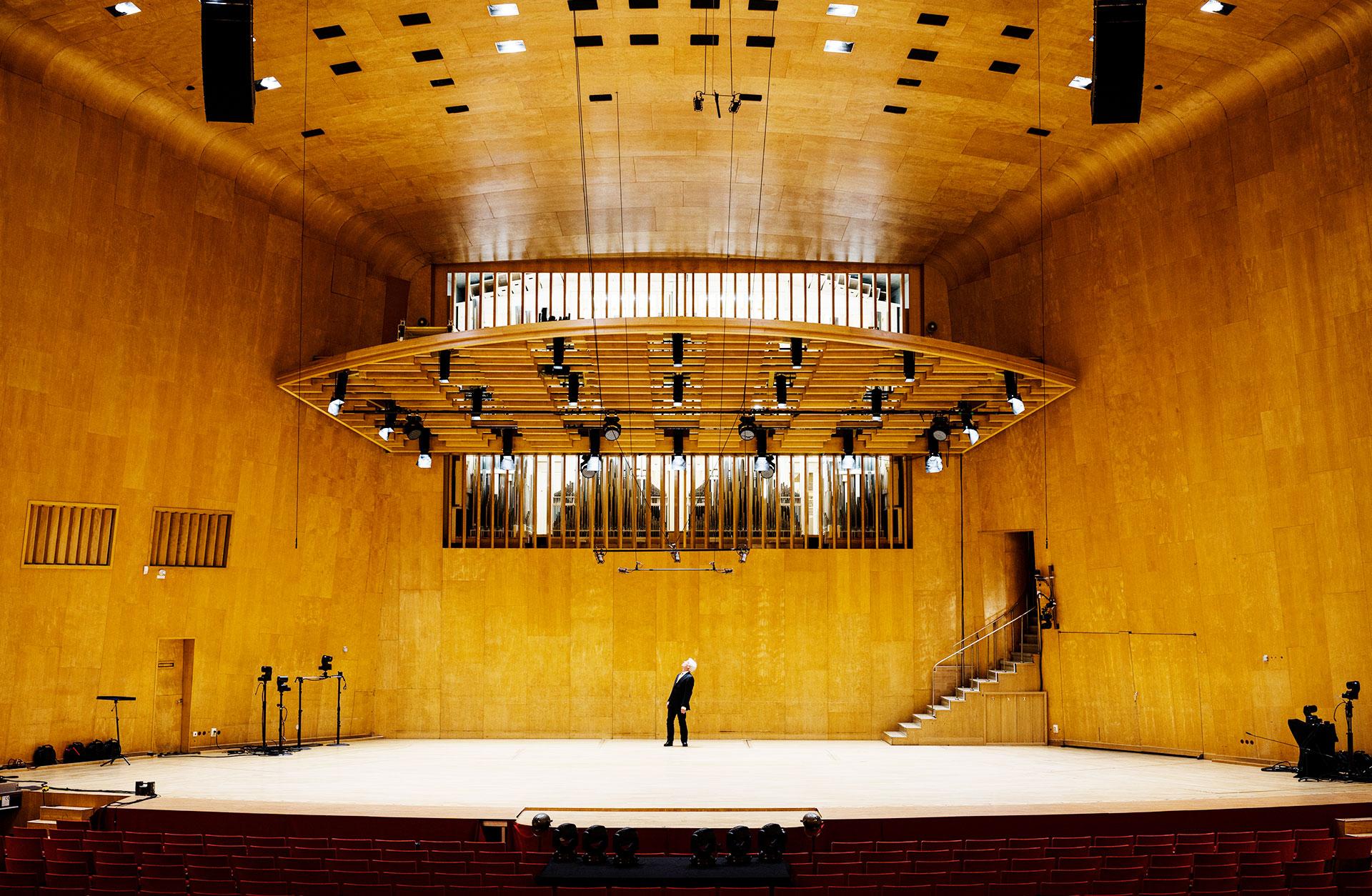 Konserthusorgeln syns genom lamellerna längst fram i konsertsalen, ovanför scenen. På scenen står en man och blickar upp mot orgeln.