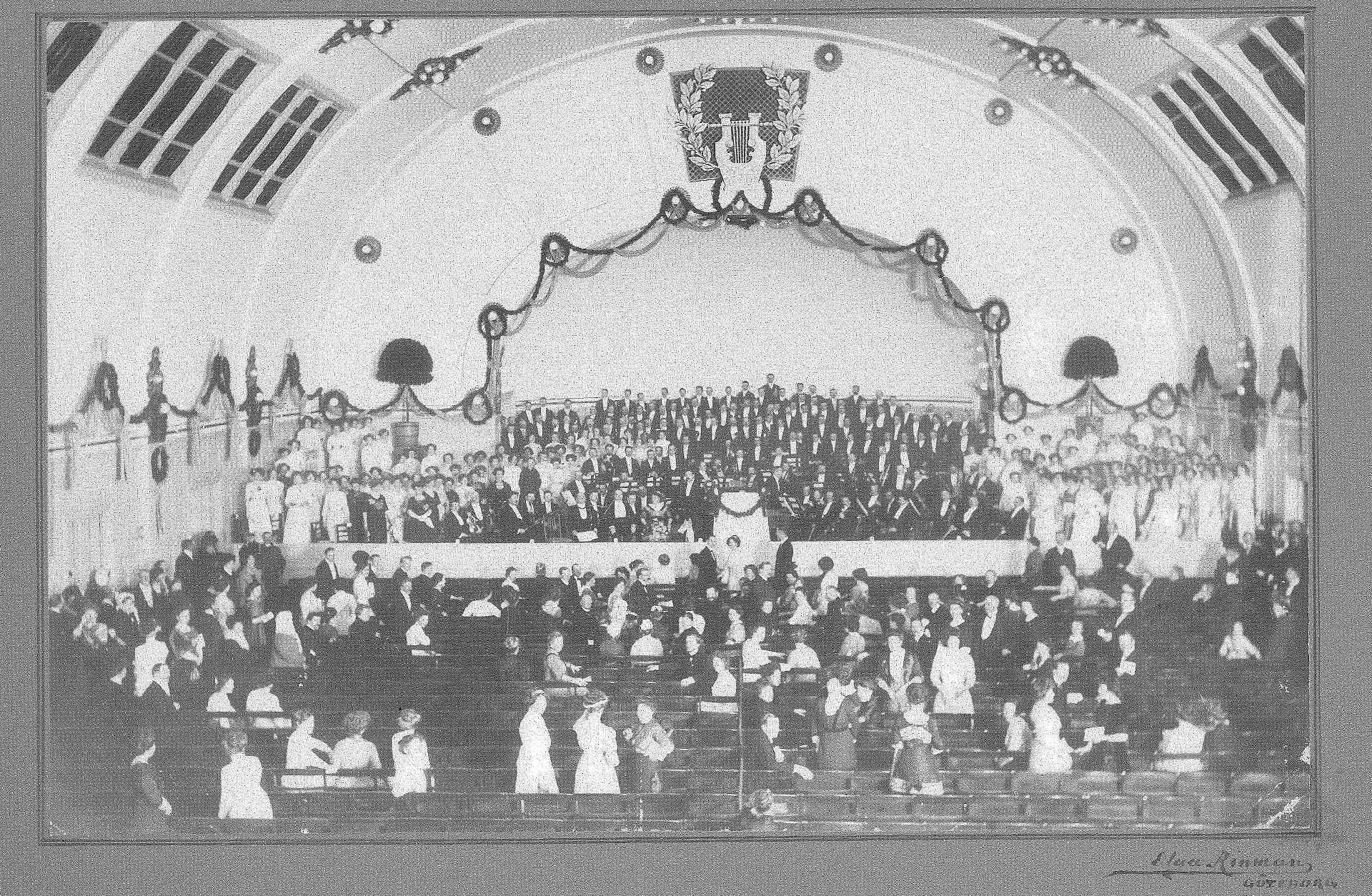 Historiskt fotografi av Göteborgs Symfoniker på scenen i konserthuset på Heden i Göteborg, med publik i förgrunden.