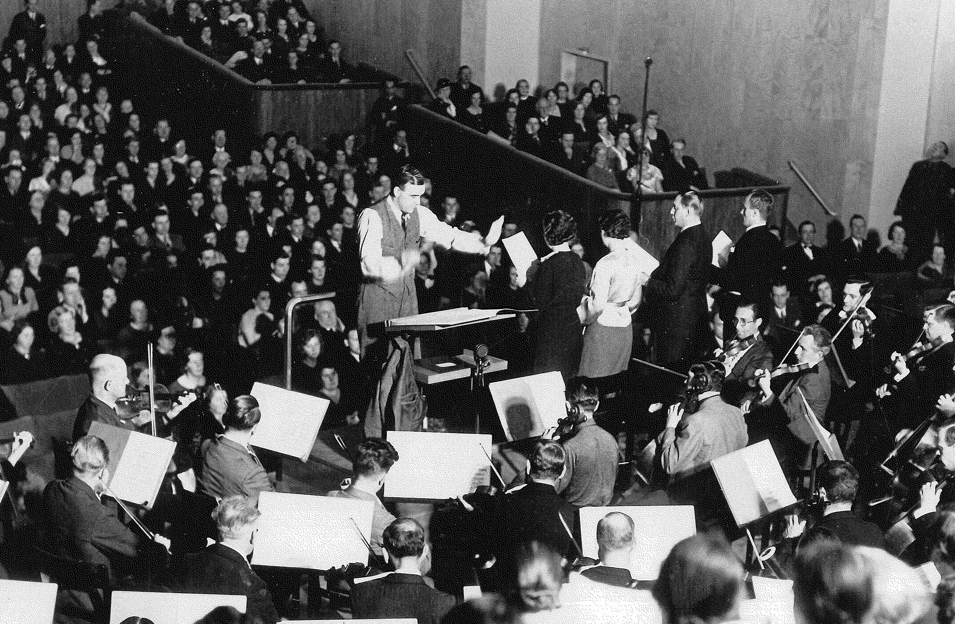 Foto av Stora salein i Göteborgs Konserthus vid invigningen 1925, dirigent framför orkester med publiken i salongen i bakgrunden.
