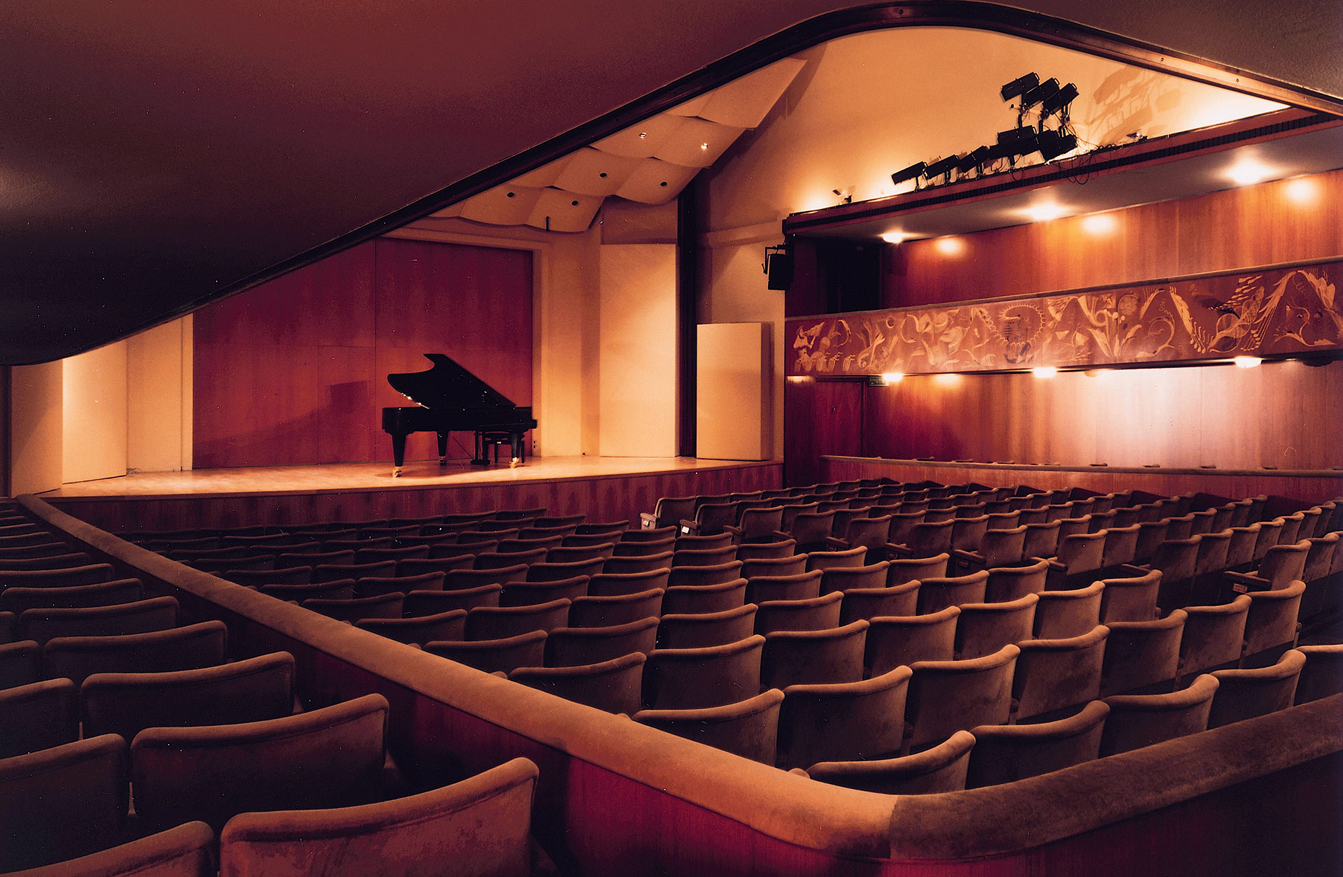 Konsertsal med stolar i förgrunden och scen med flygel.