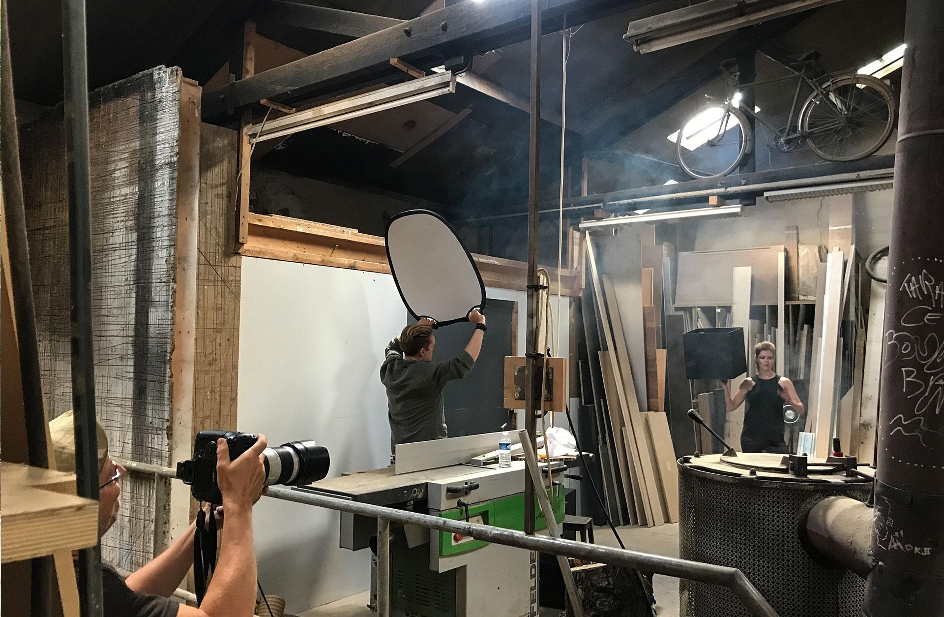 Mats Bäcker fotograferar Barbara som poserar med den svarta lådan i en hand. Linus håller en reflektor. miljön är stökig.
