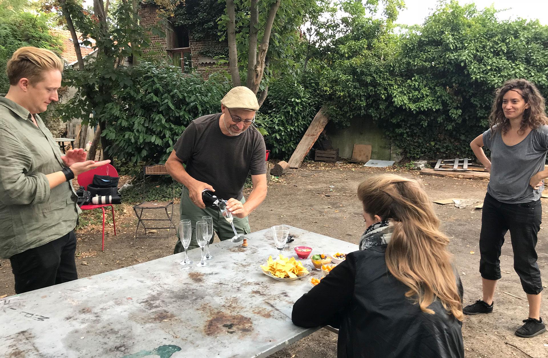 Utomhus i trädgården. Mats häller upp champagne i fem glas. Linus, Julia och Barbara är också där.