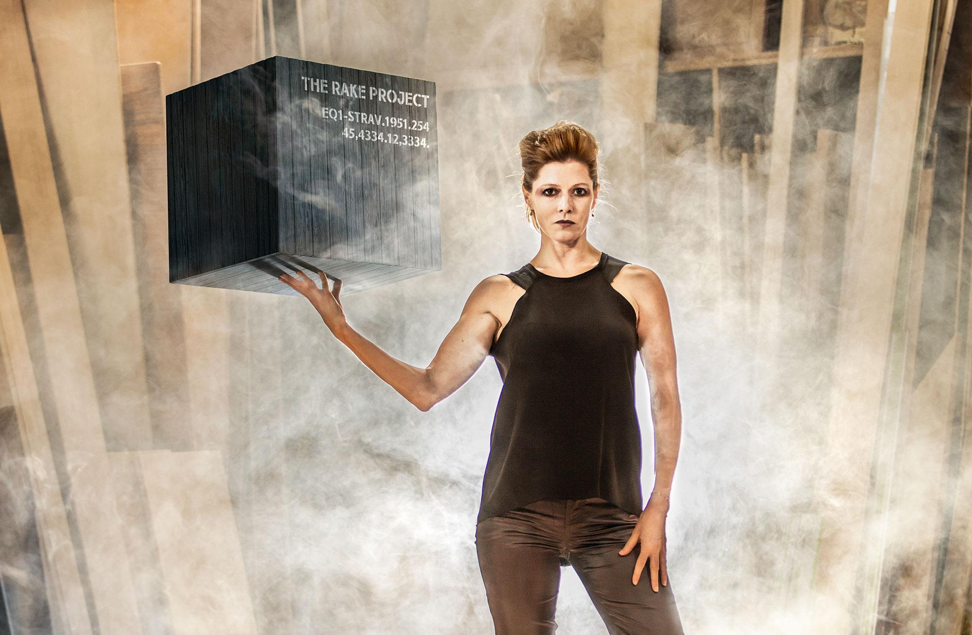 Dirigenten Barbara Hannigan står mot en ruffig fond. Hon håller en stor svart låda i handen med texten The Rake Project. Rummet är fyllt av rök.