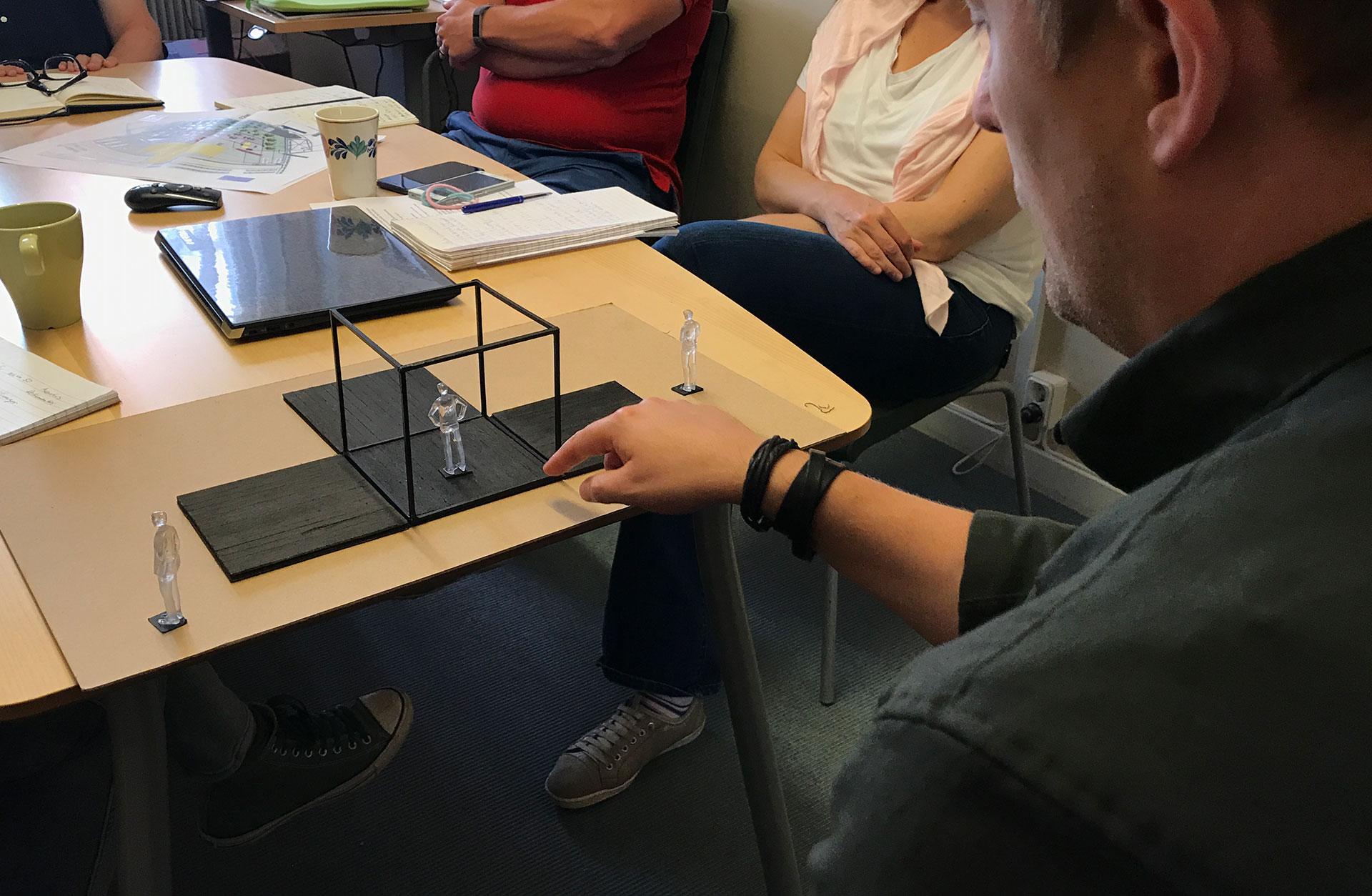 Regissörens Linus Fellbom sitter vid ett bord med människor runt om, och visar upp scenmodellen.