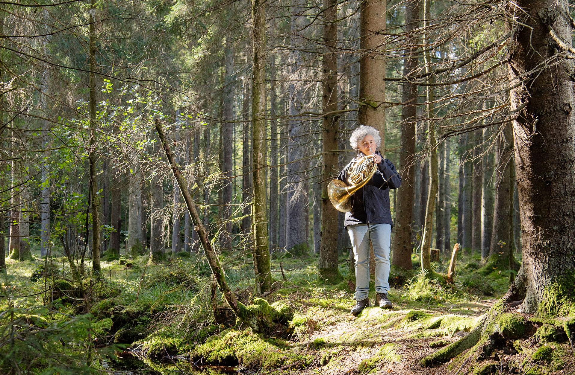 Lisa ford står i skogen och spelar på sitt horn.