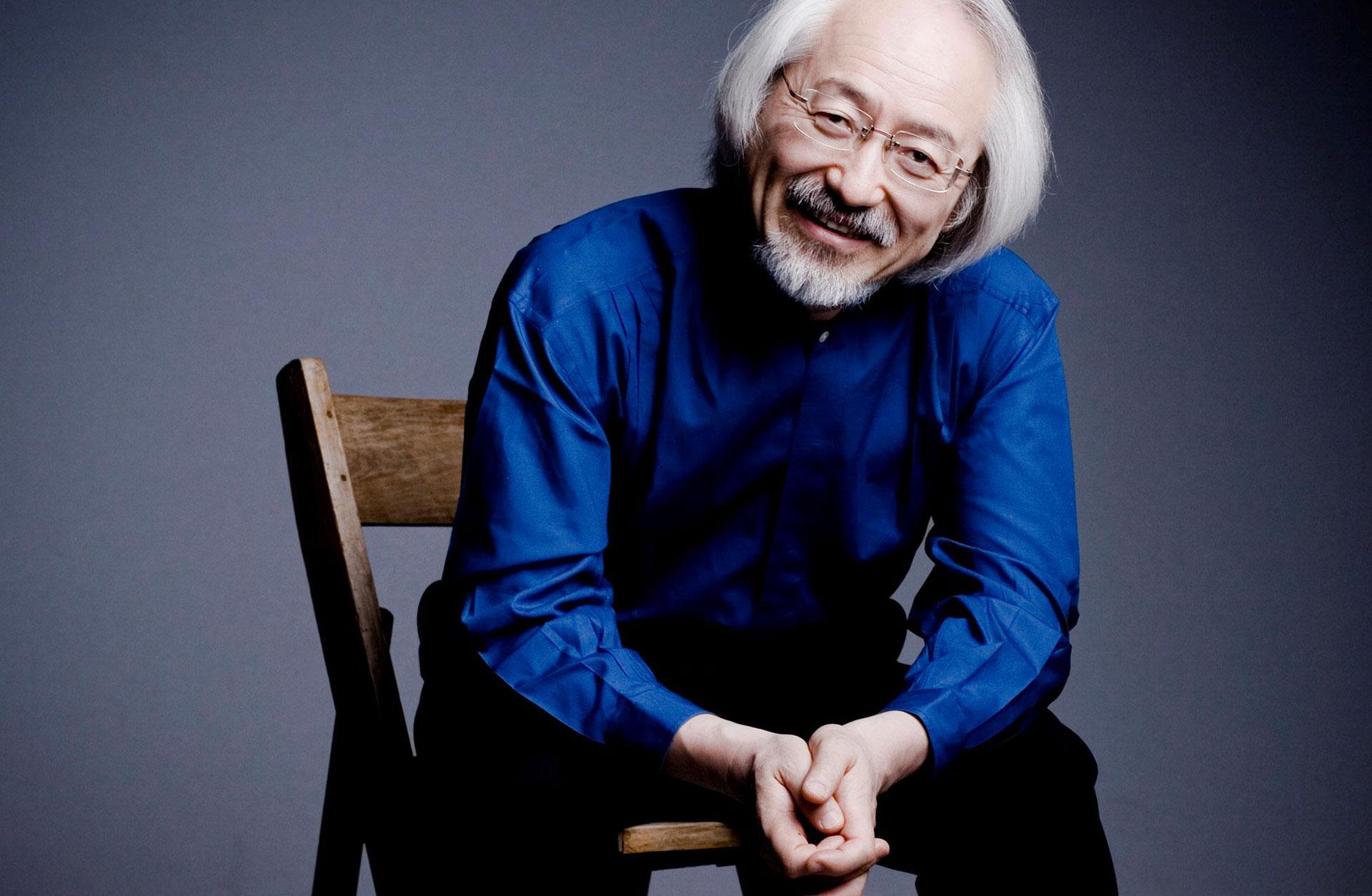 Masaaki Suzuki sitter på en stol. Han ler mot kameran.