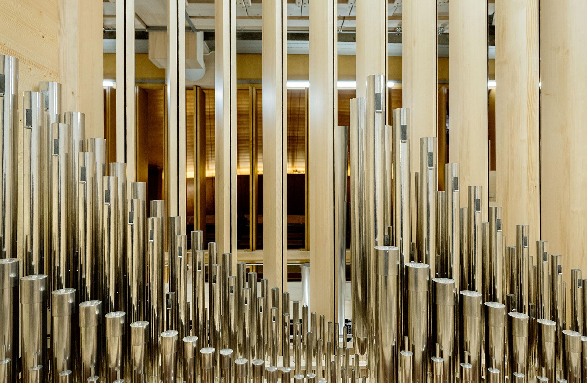 Orgelpipor från insidan av orgeln, publikplatserna anas genom lamellerna bakom piporna.