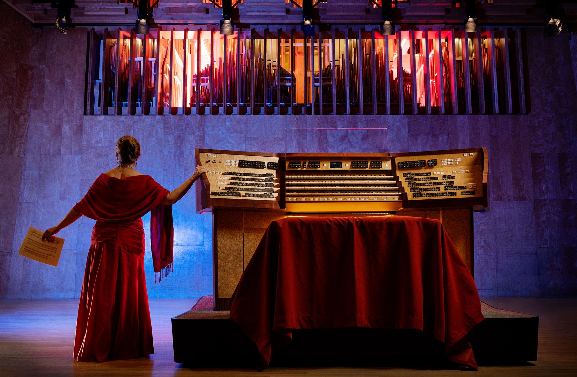 Orgelns spelbord och musiker på scenen i vacker ljussättning, piporna anas bakom lamellerna i fonden.