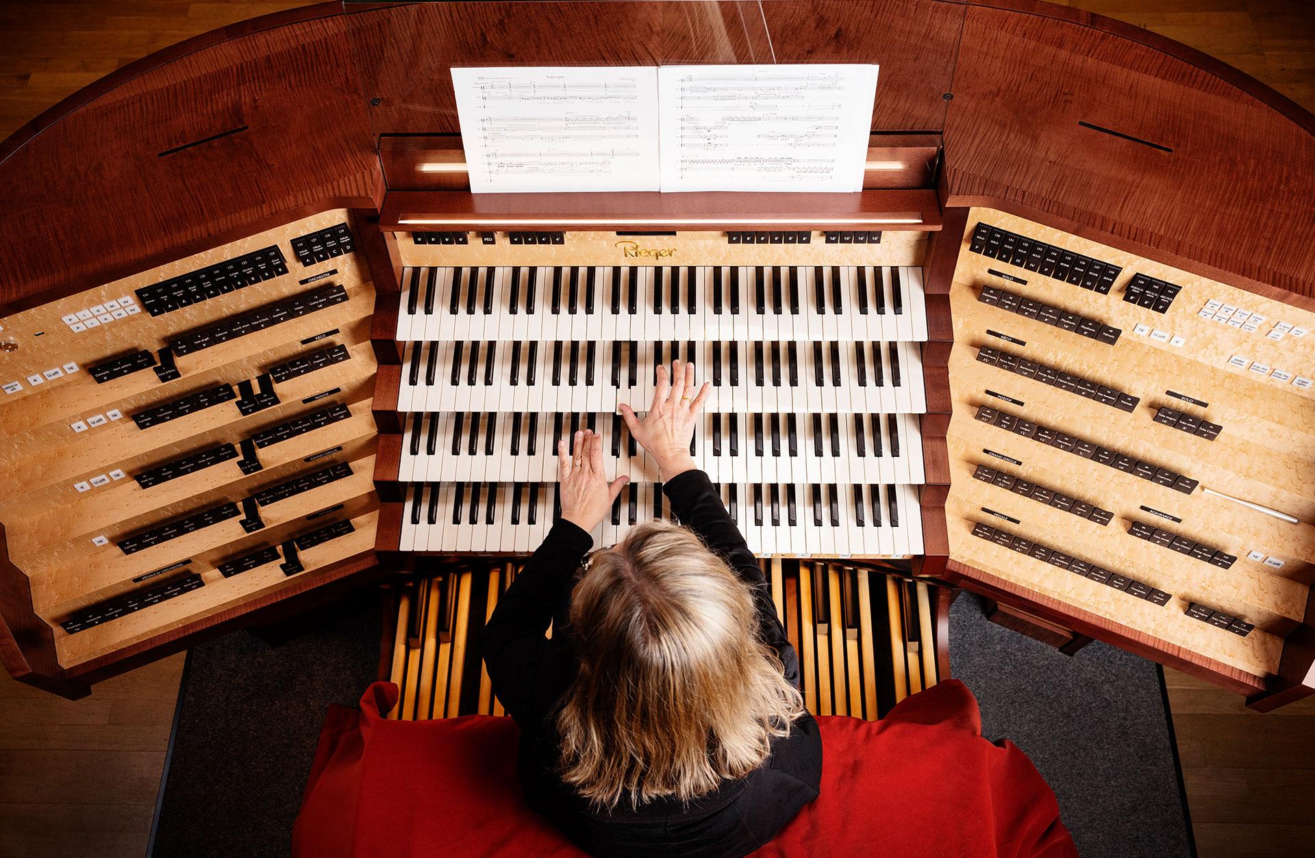 Orgelns spelbord ovanifrån med en mängd tangenter och knappar som musikerns händer vilar på.