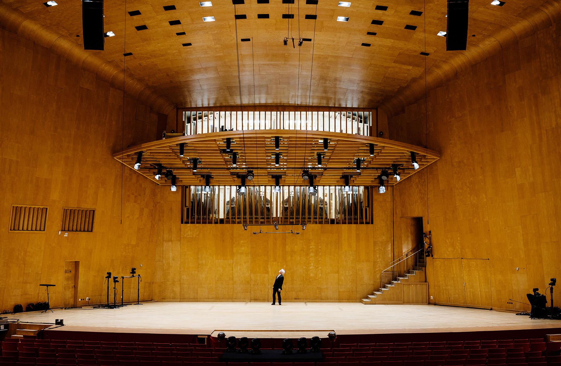Konserthusorgeln syns mellan lammellerna längst fram i konsertsalen, ovanför scenen. På scenen står en man och blickar upp mot orgeln.