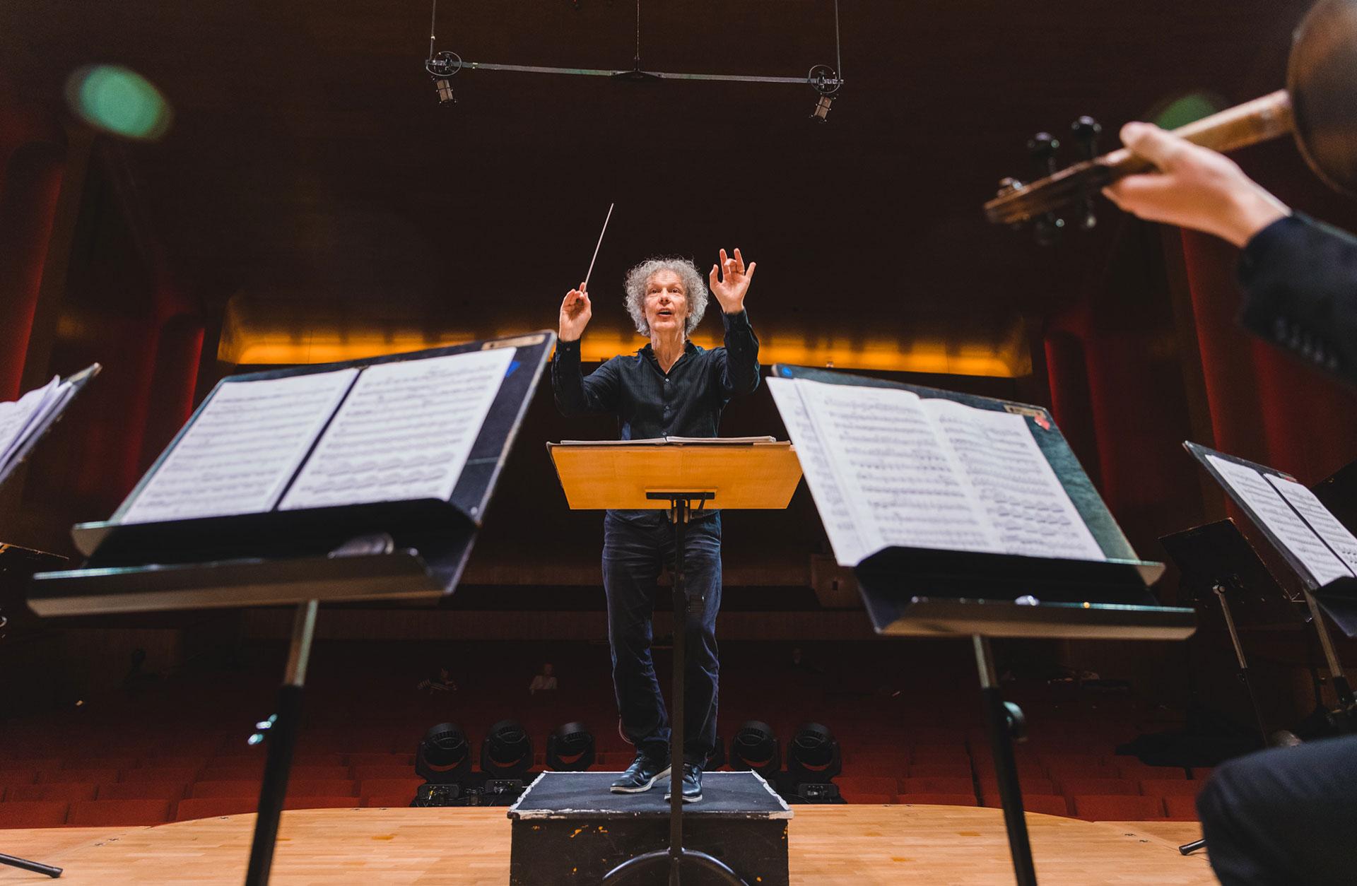 Dirigenten Simon Phipps dirigerar framför orkestern.