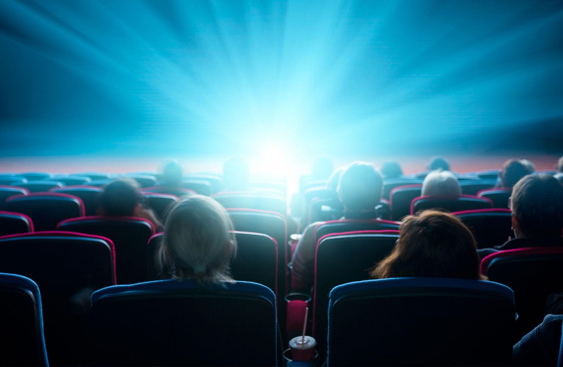 Publik sitter i en biosalong med motljus.
