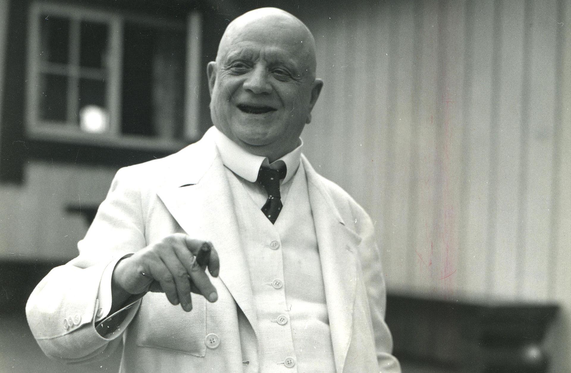 En vitklädd Jean Sibelius skrattar med cigarr i handen.
