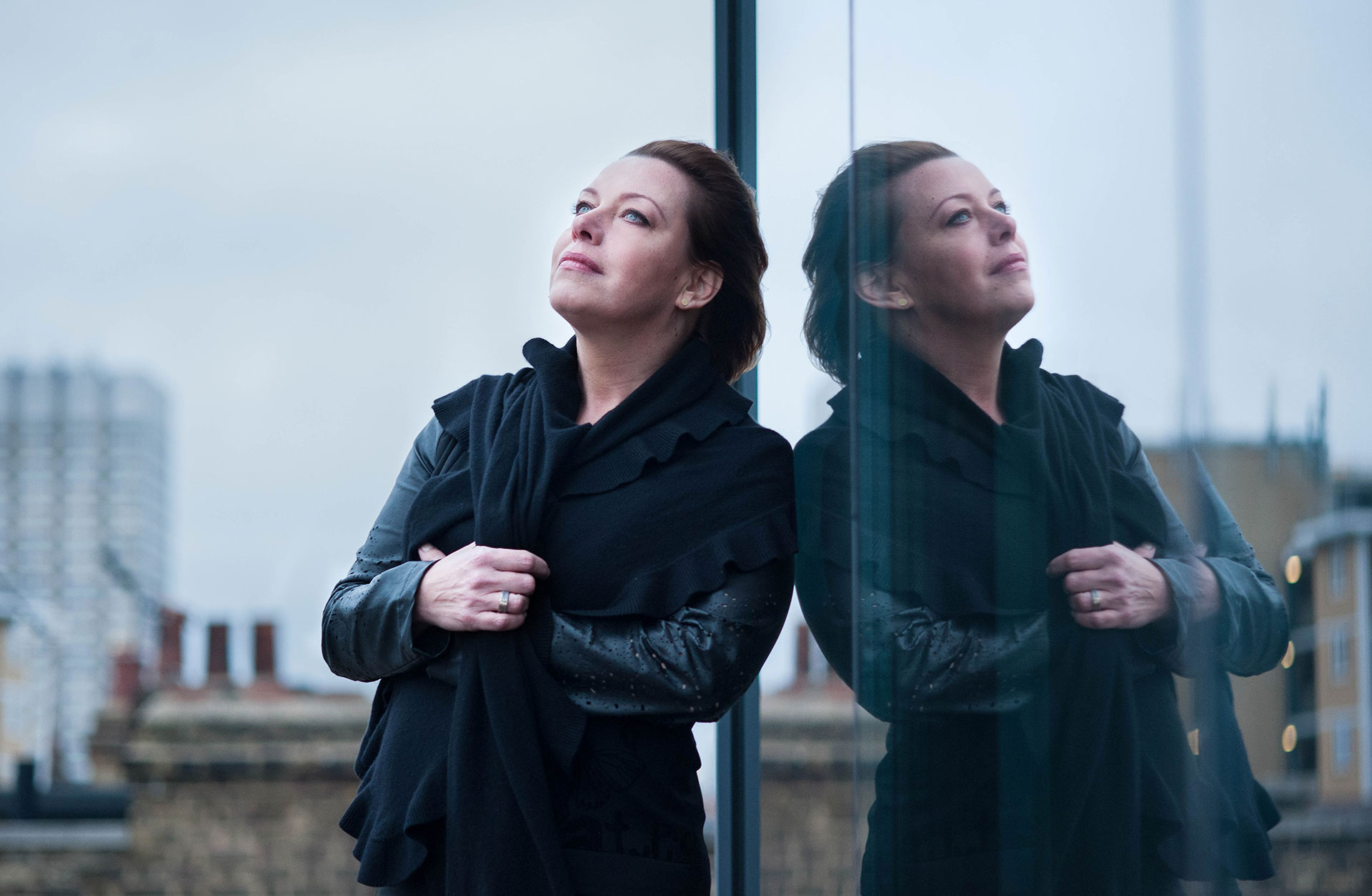 Nina Stemme står lutad mot ett fönster, utomhus. Hennes spegelbild reflekteras i fönstret.
