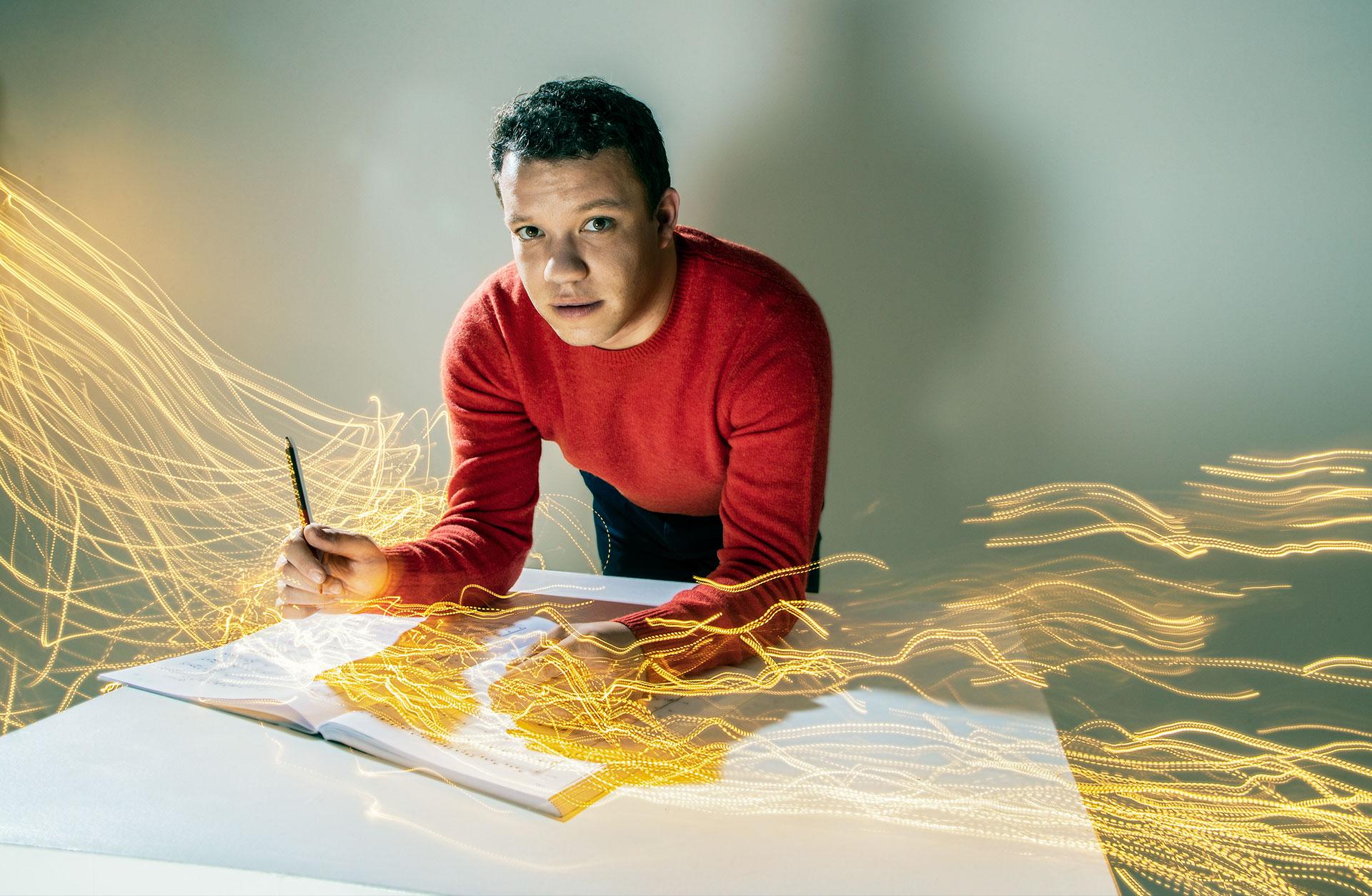 Dirigenten Ryan Bancroft lutar sig över ett notblad med pennan i hand, det går ljusstrålar från notbladet.