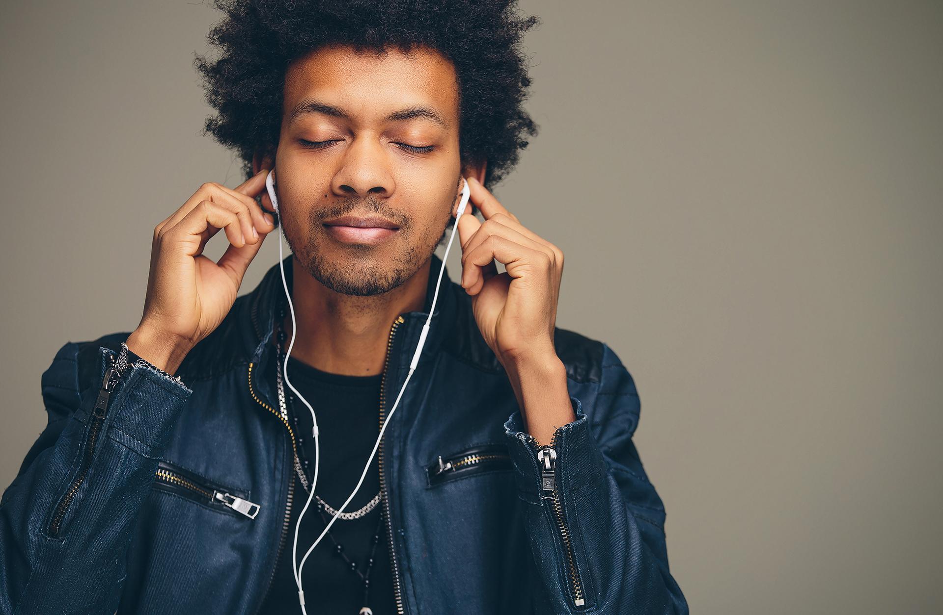 Kille med svart hår njuter av musik i hörlurar