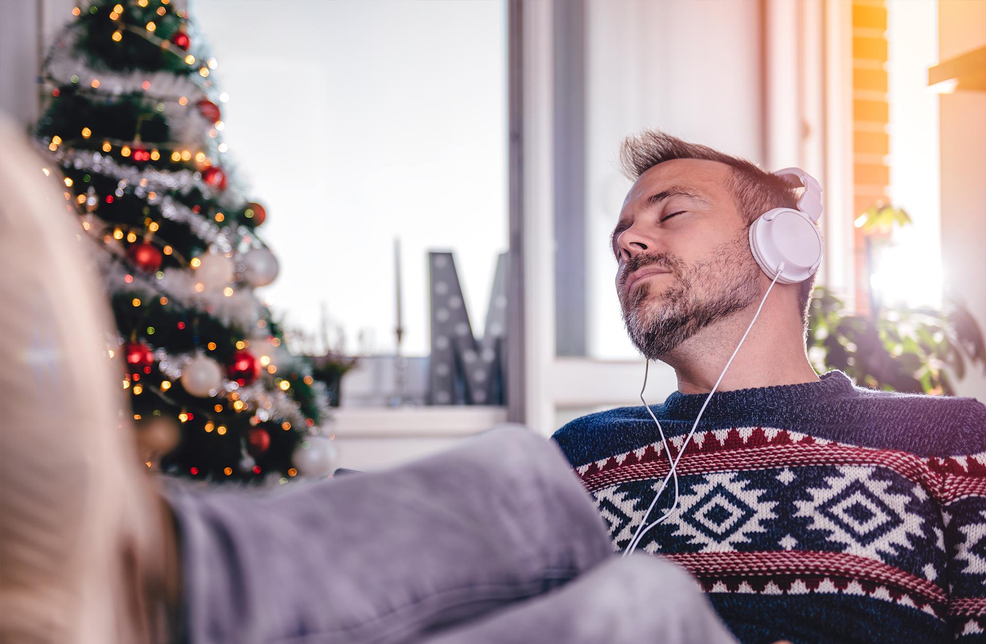 Man i jultröja njuter med hörlurar