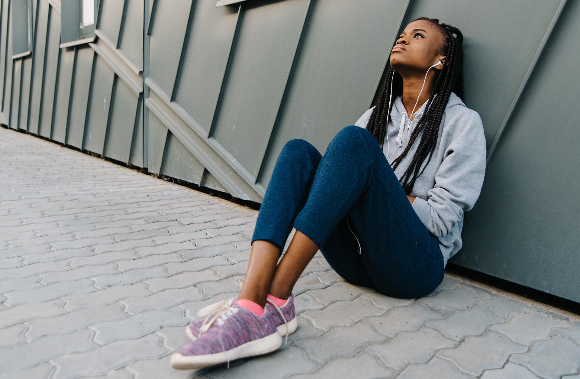 Kvinna sitter på marken och ser grubblande ut med hörlurar