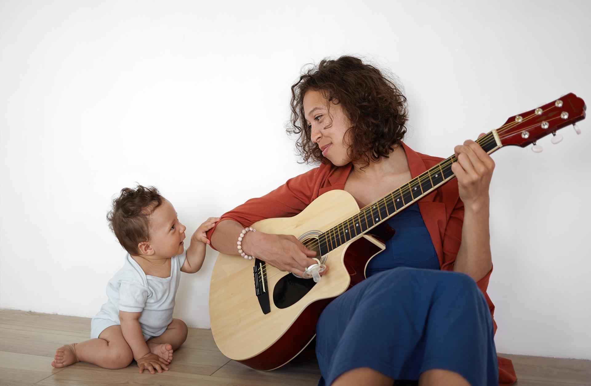 Kvinna spelar gitarr tillsammans med sitt barn