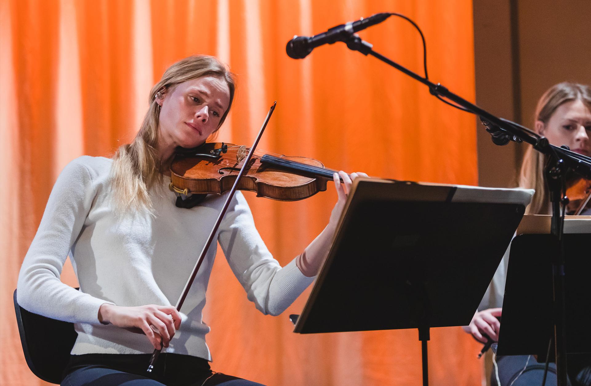 Ljushårig kvinna spelar fiol
