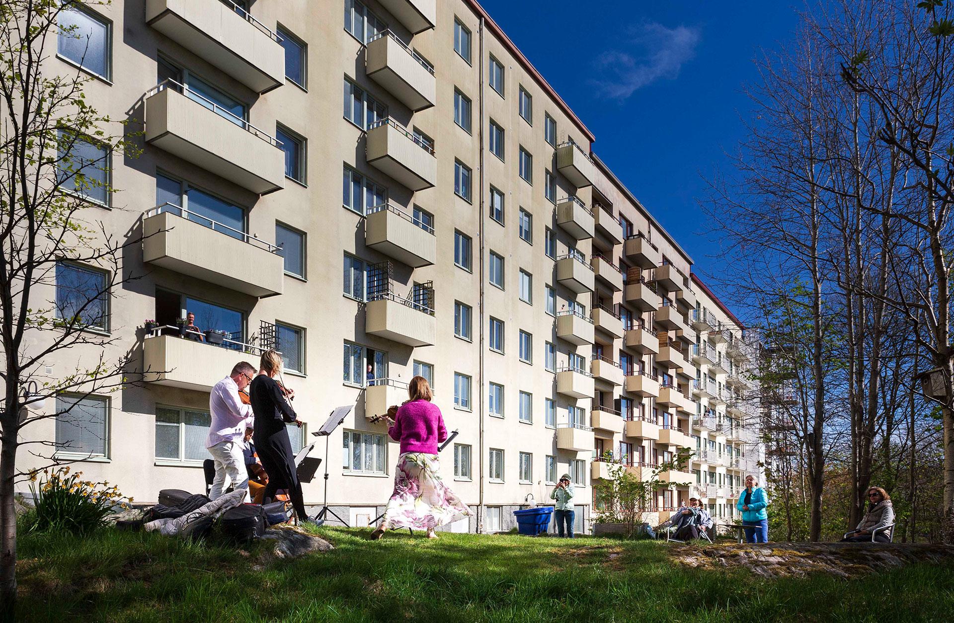 En kvartett från Göteborgs Symfoniker spelar utanför ett höghus. Människor lyssnar från fönstren och står runt om på gården.