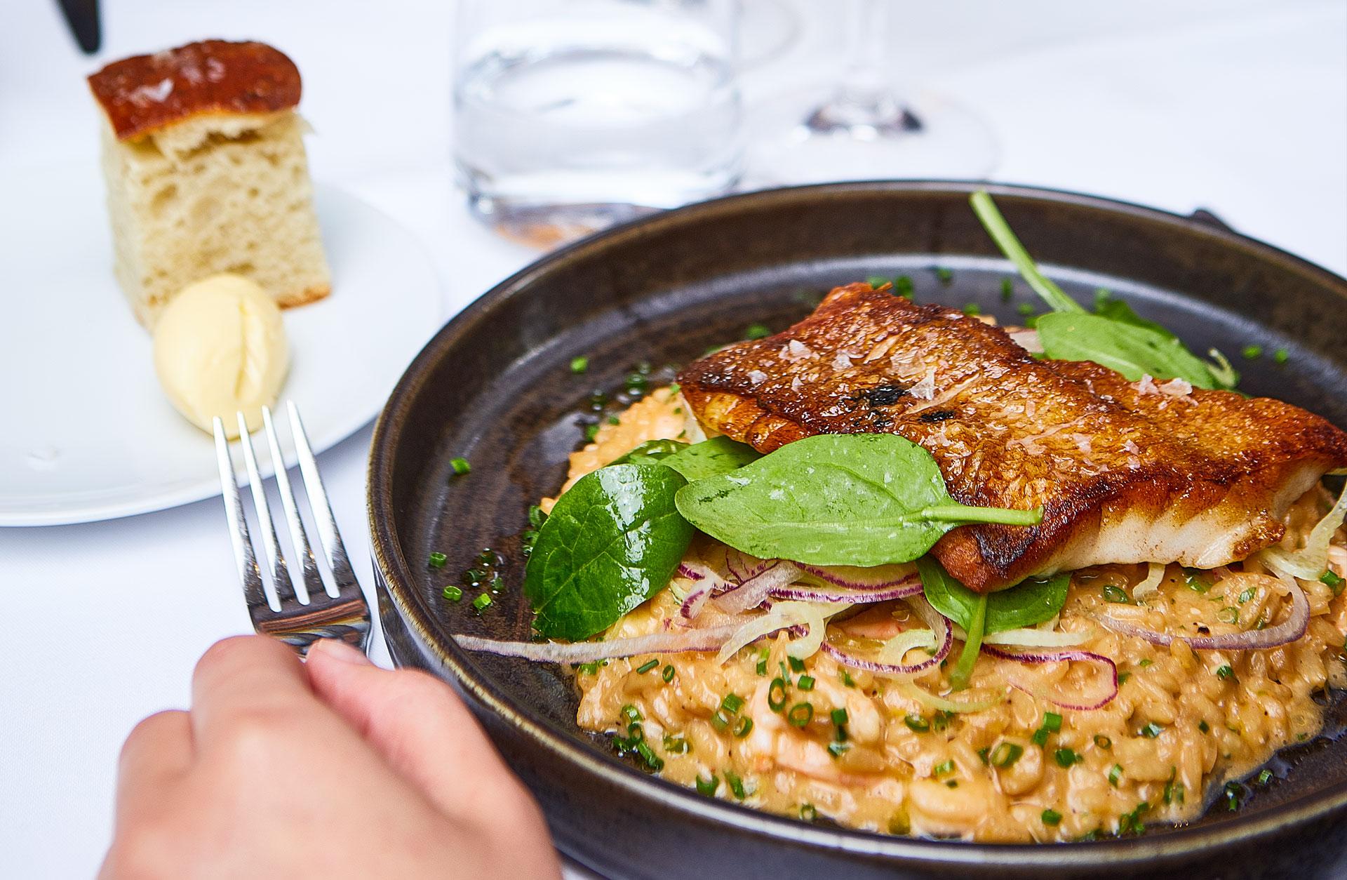 Tallrik med skaldjursrisotto med fisk uppdukat på bord med vit duk.