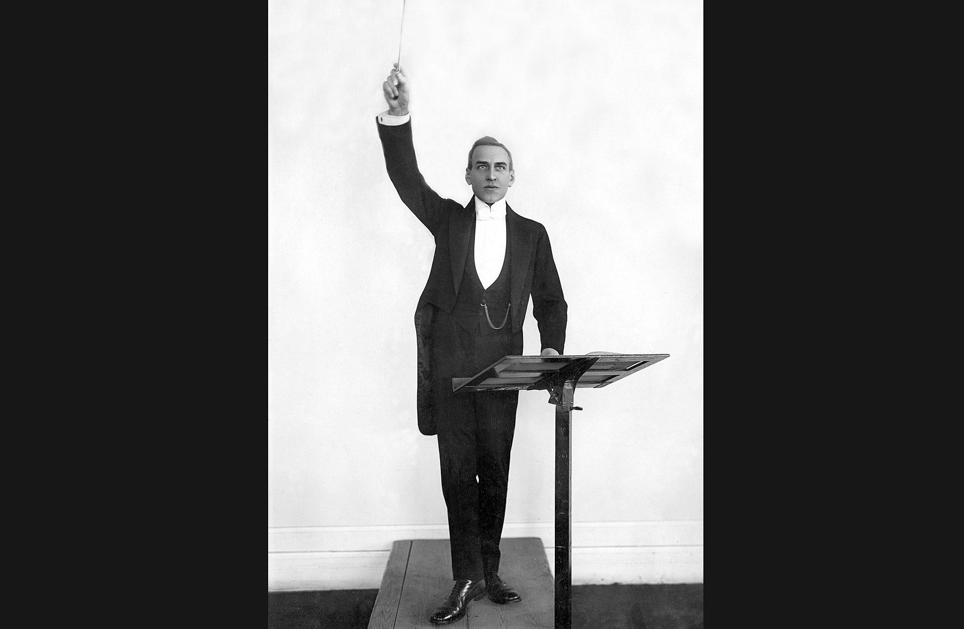 Dirigenten Stenhammar på podiet med taktpinnen höjd över huvudet.