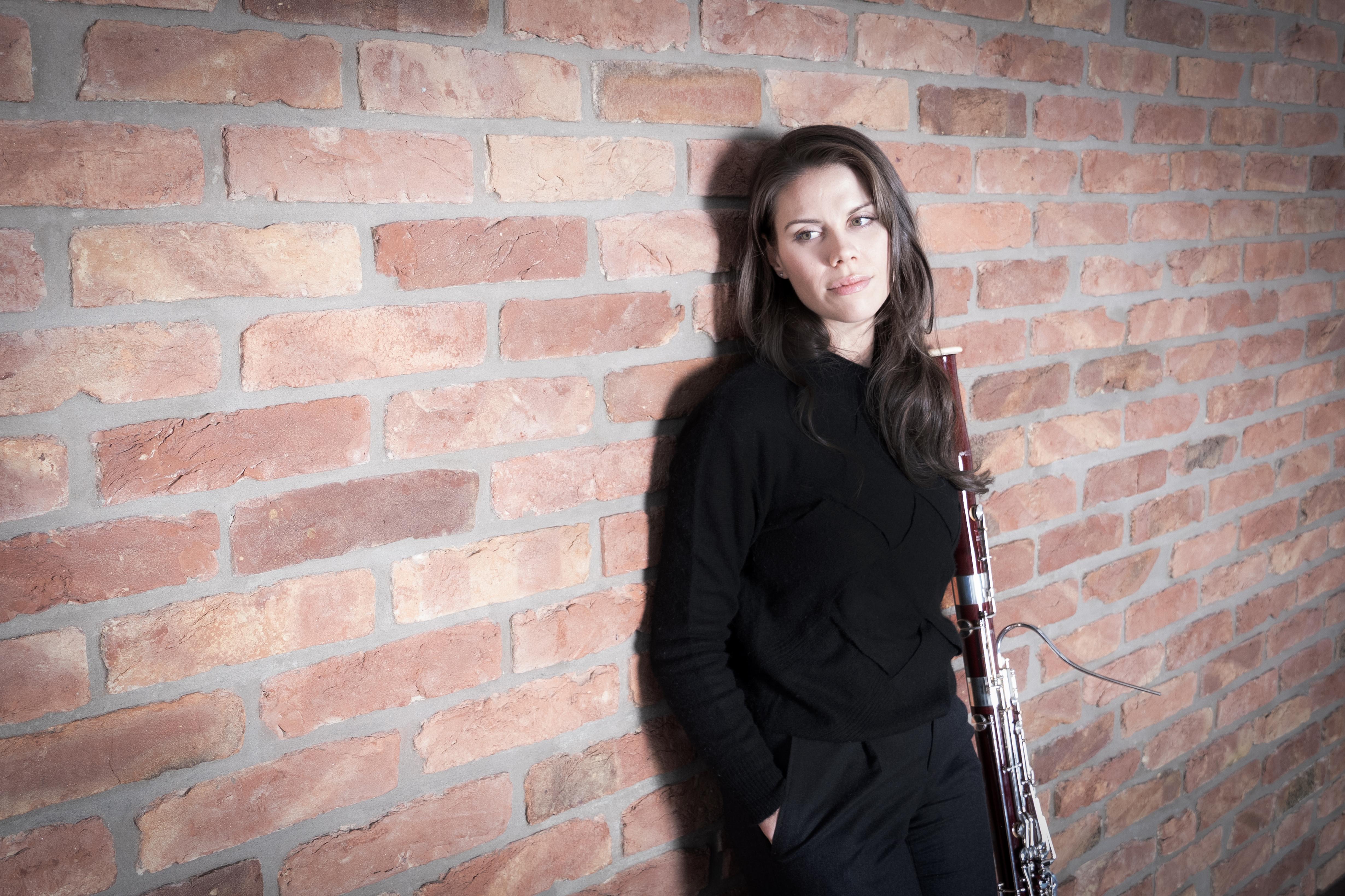 Kaitlyn Cameron, klädd i svarta kläder, lutar sig mot en tegelvägg.