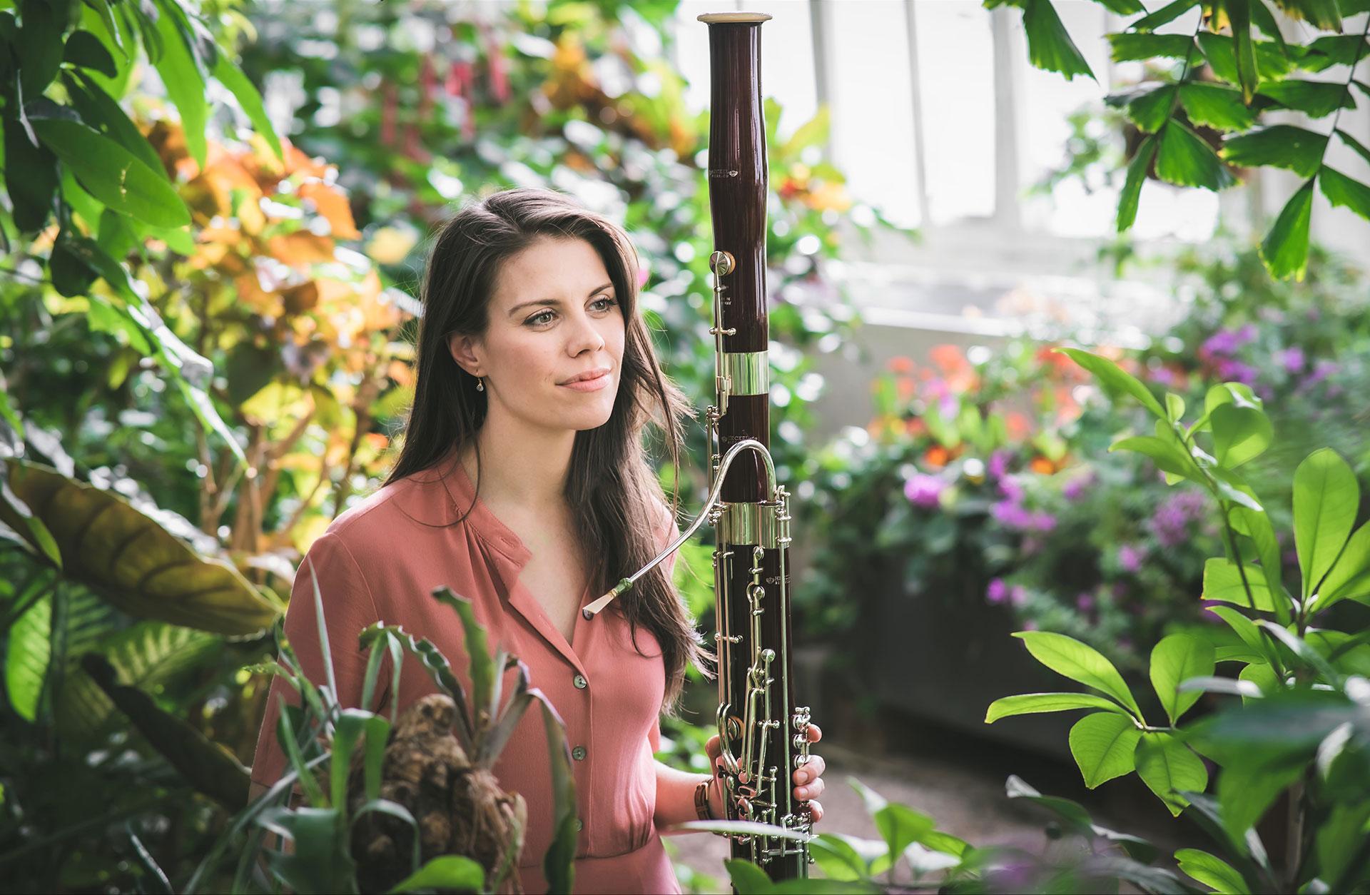 Kaitlyn Cameron, klädd i klänning, håller sin fagott bland träd och blad i Wiens palmhus.
