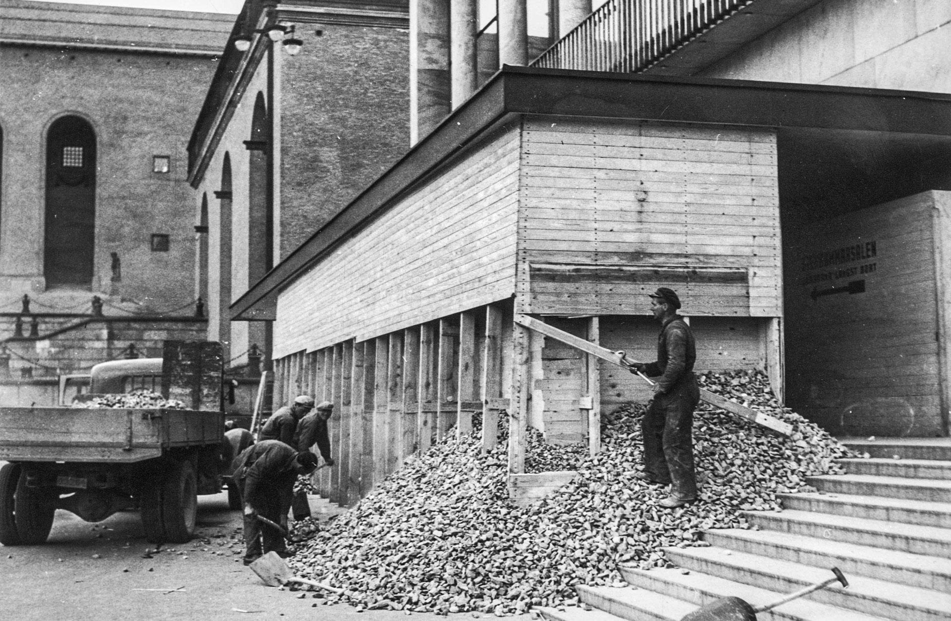 Fyra byggarbetare river en provisoriskt ubbyggd vägg av plank, fylld med småsten, på trappan vid entrén till Konserthuset.