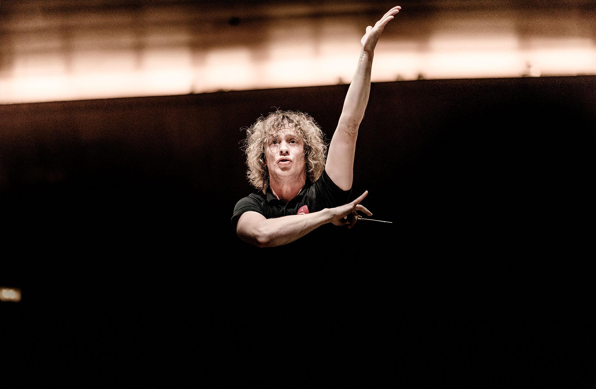 Dirigent Santtu-Matias Rouvali på podiet med taktpinnen i handen, ena armen kraftfullt riktad mot taket.
