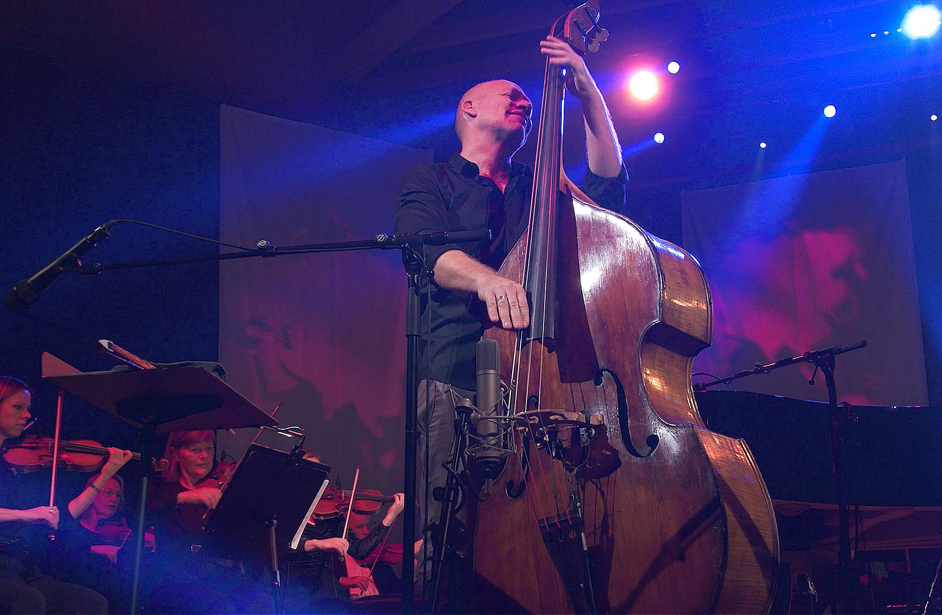 Jazzbasisten Avishai Cohen på scenen i blått ljus tillsammans med Symfonikerna, han ser nöjd ut.