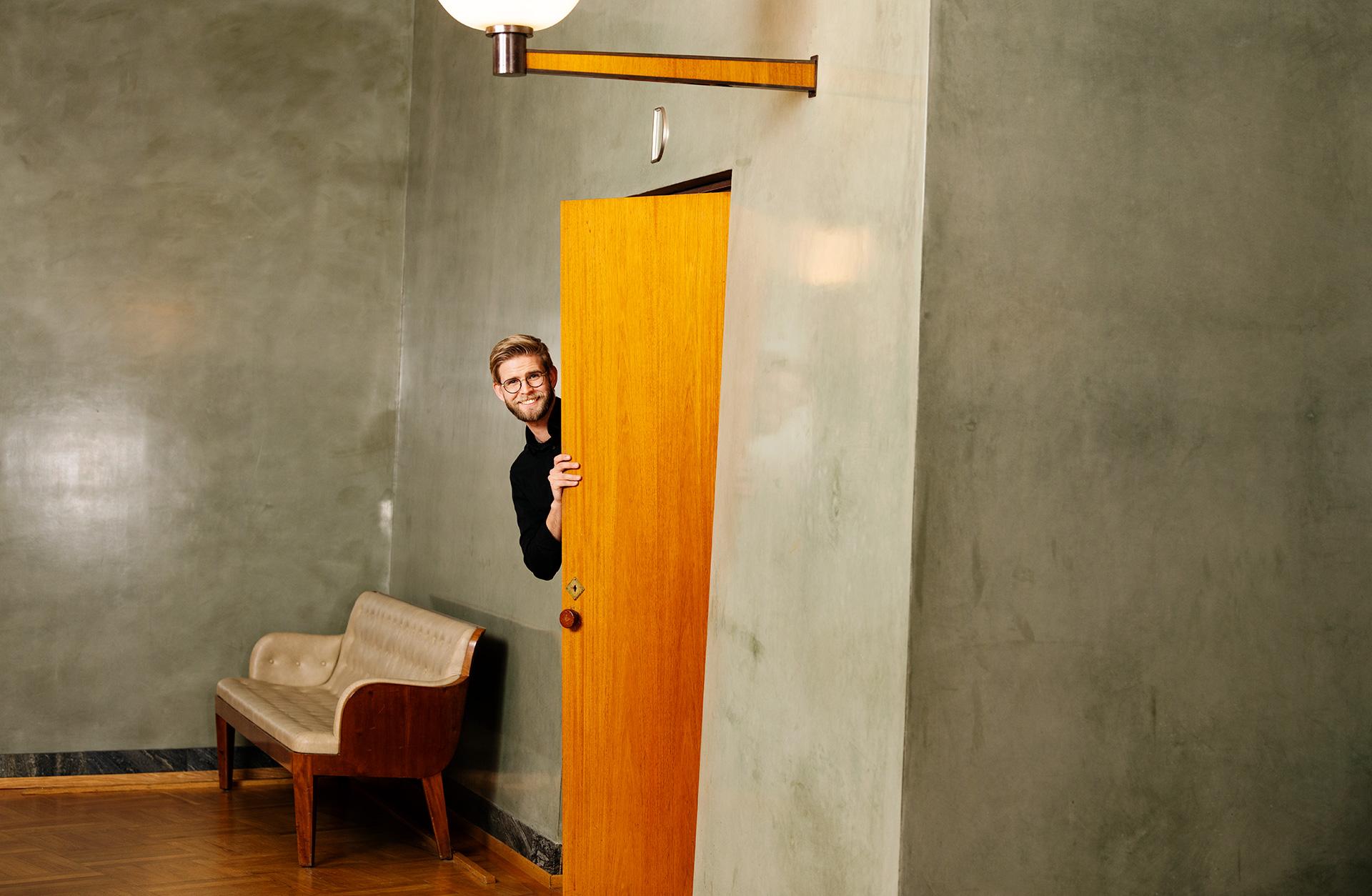 En medelålders kille tittar ut genom en dörr i konserthuset