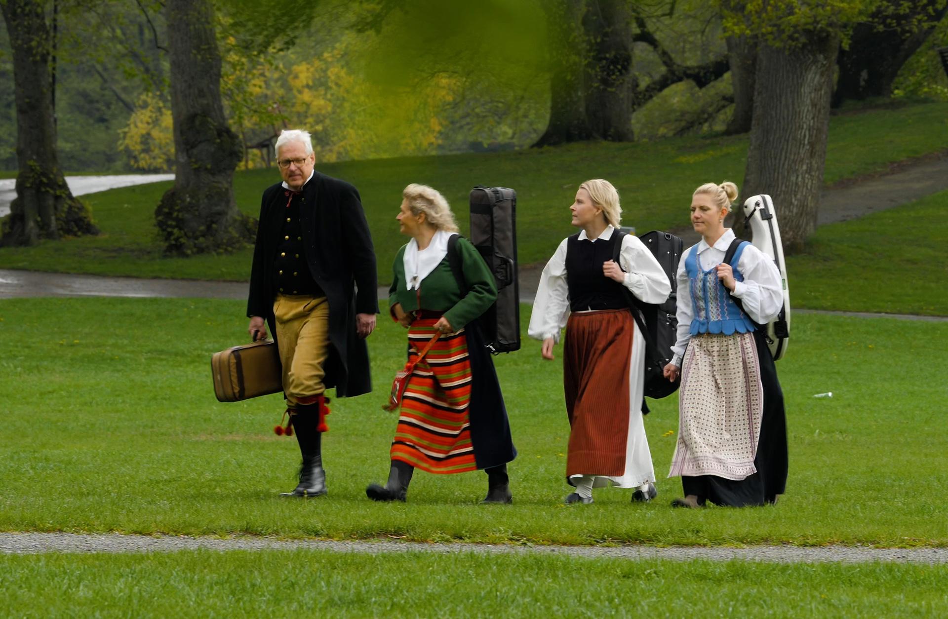 Fyra musiker i folkdräkt går över en gräsmatta