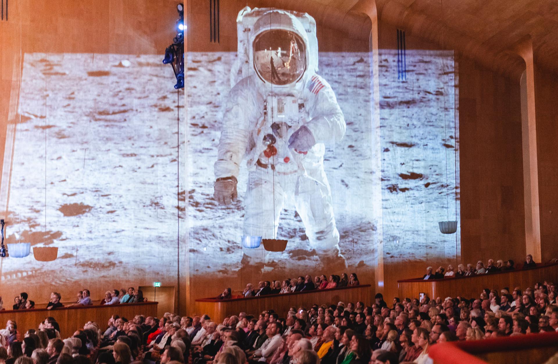 Stora salen fylld med publik och projektorbild på månlandning