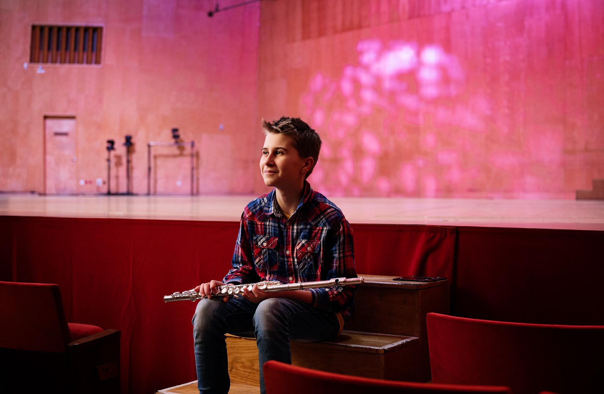 Yngre grabb sitter i ett rosa ljus i Stora Salen med en tvärflöjt
