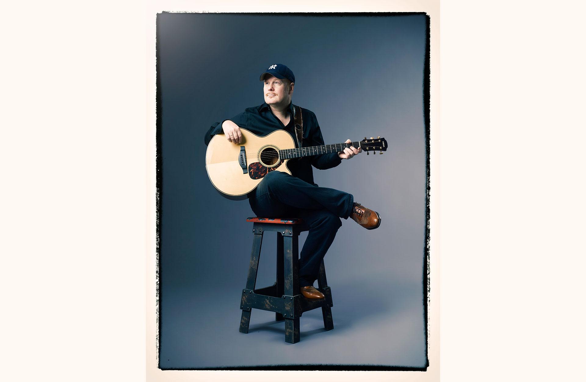 Ulf Wakenius sitter på en barstol med gitarren i famnen.
