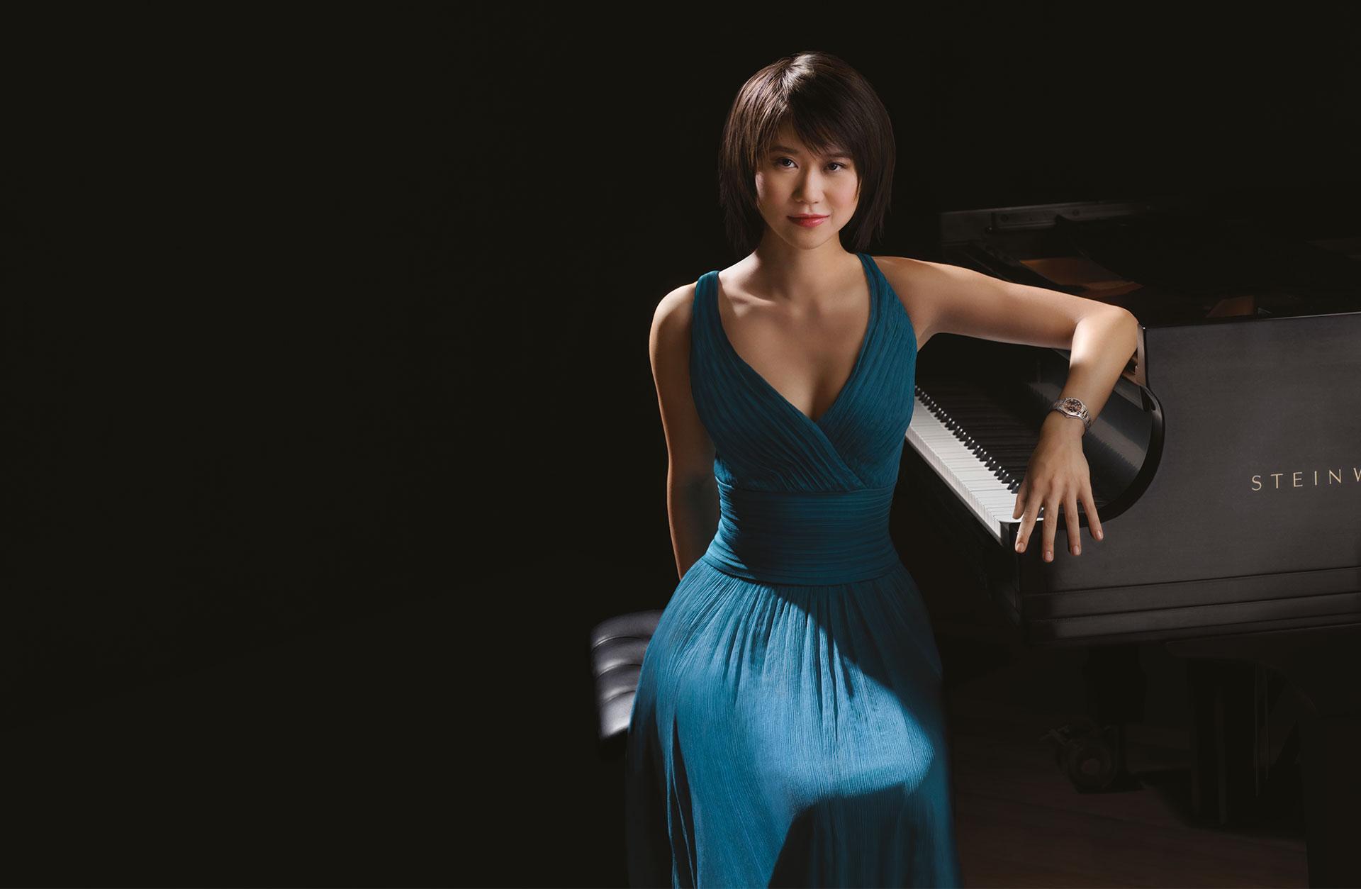 Yuja Wang, iklädd blå aftonklänning, sitter vid ett piano.