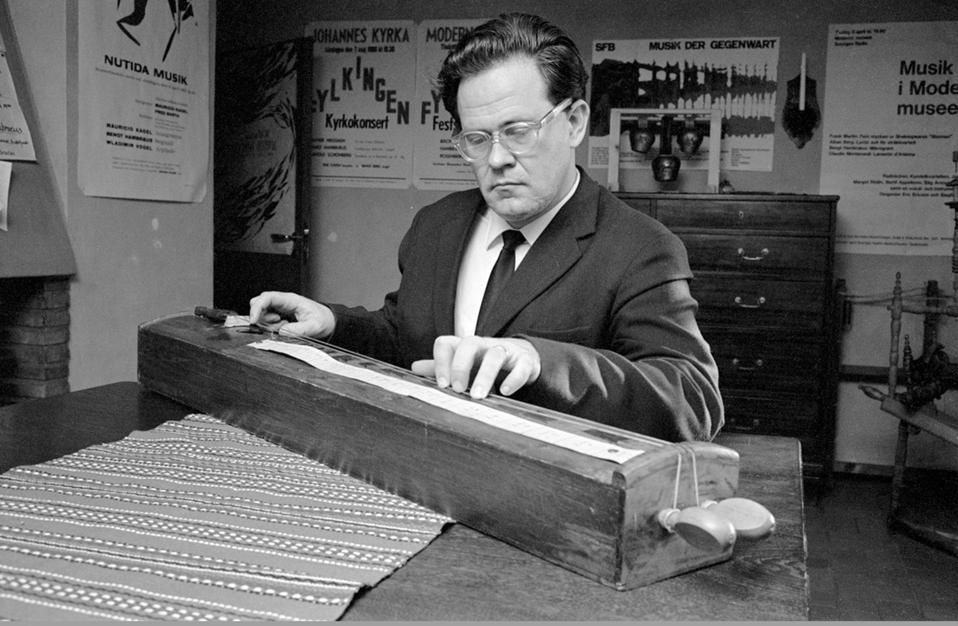 Svartvitt foto av Bengt Hambreus vid ett stränginstrument.
