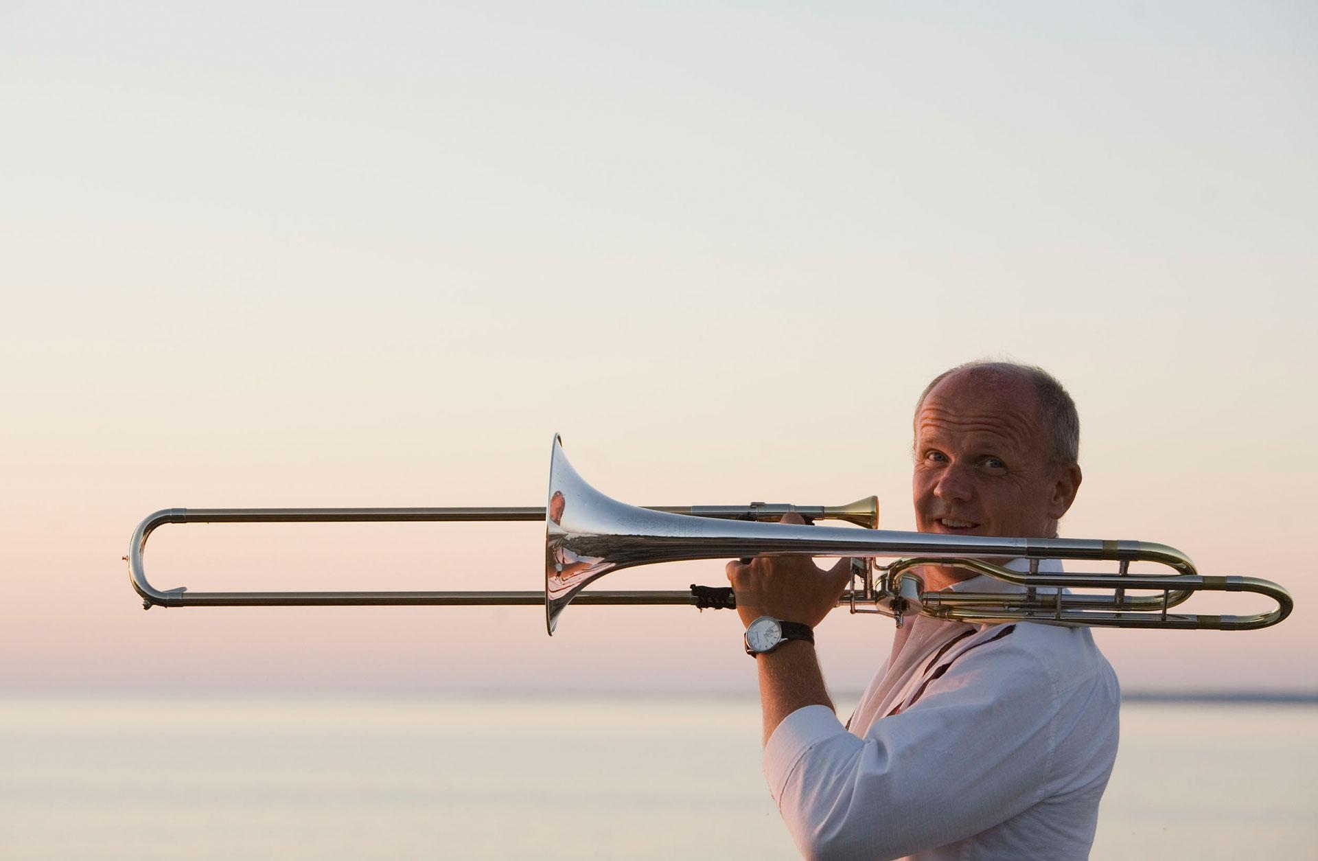 Christian Lindberg håller upp trombonen och tittar in i kameran. Havet syns i bakgrunden.