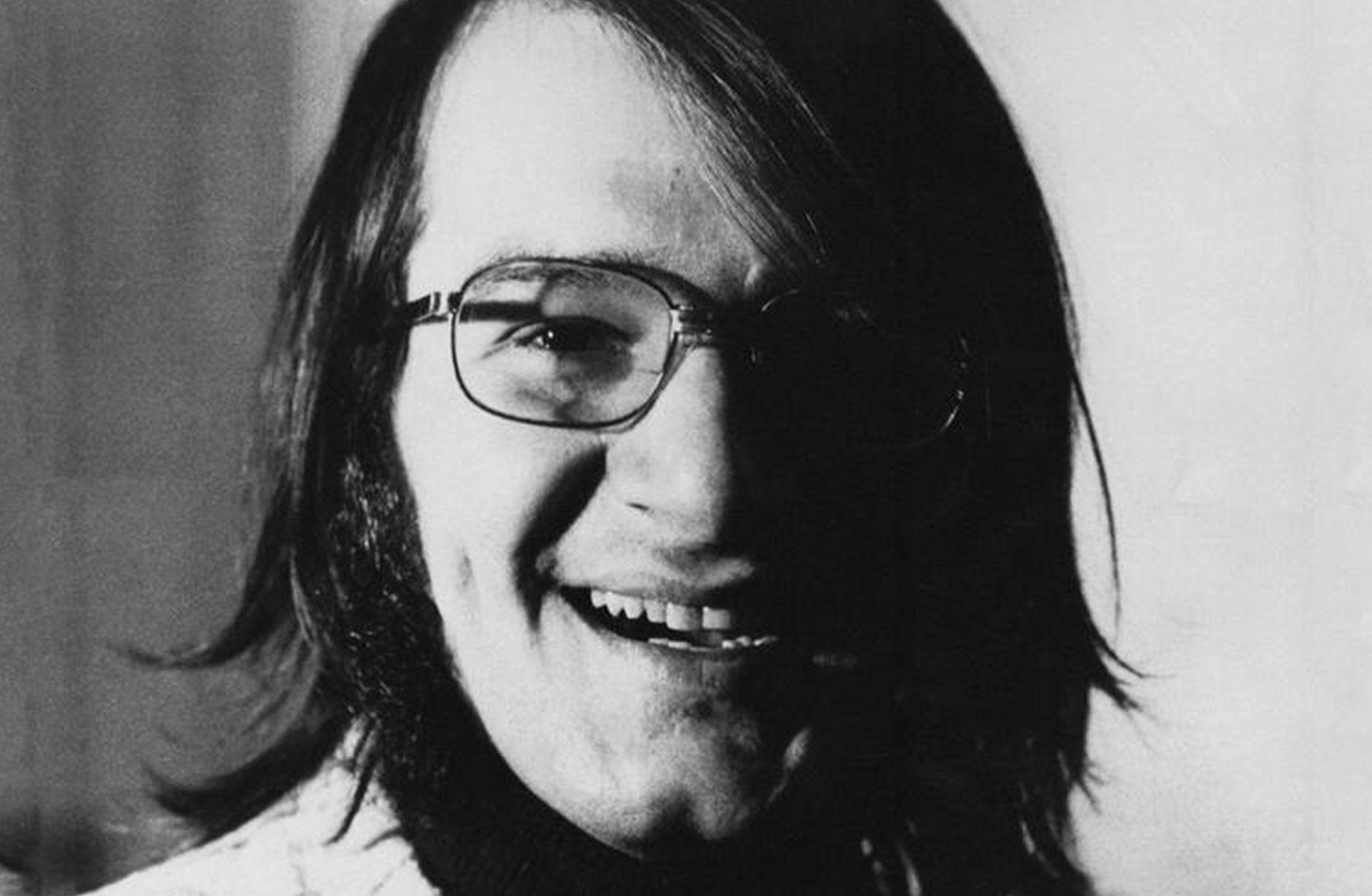 Svartvitt foto av en glad Claude Vivier som skrattar mot kameran