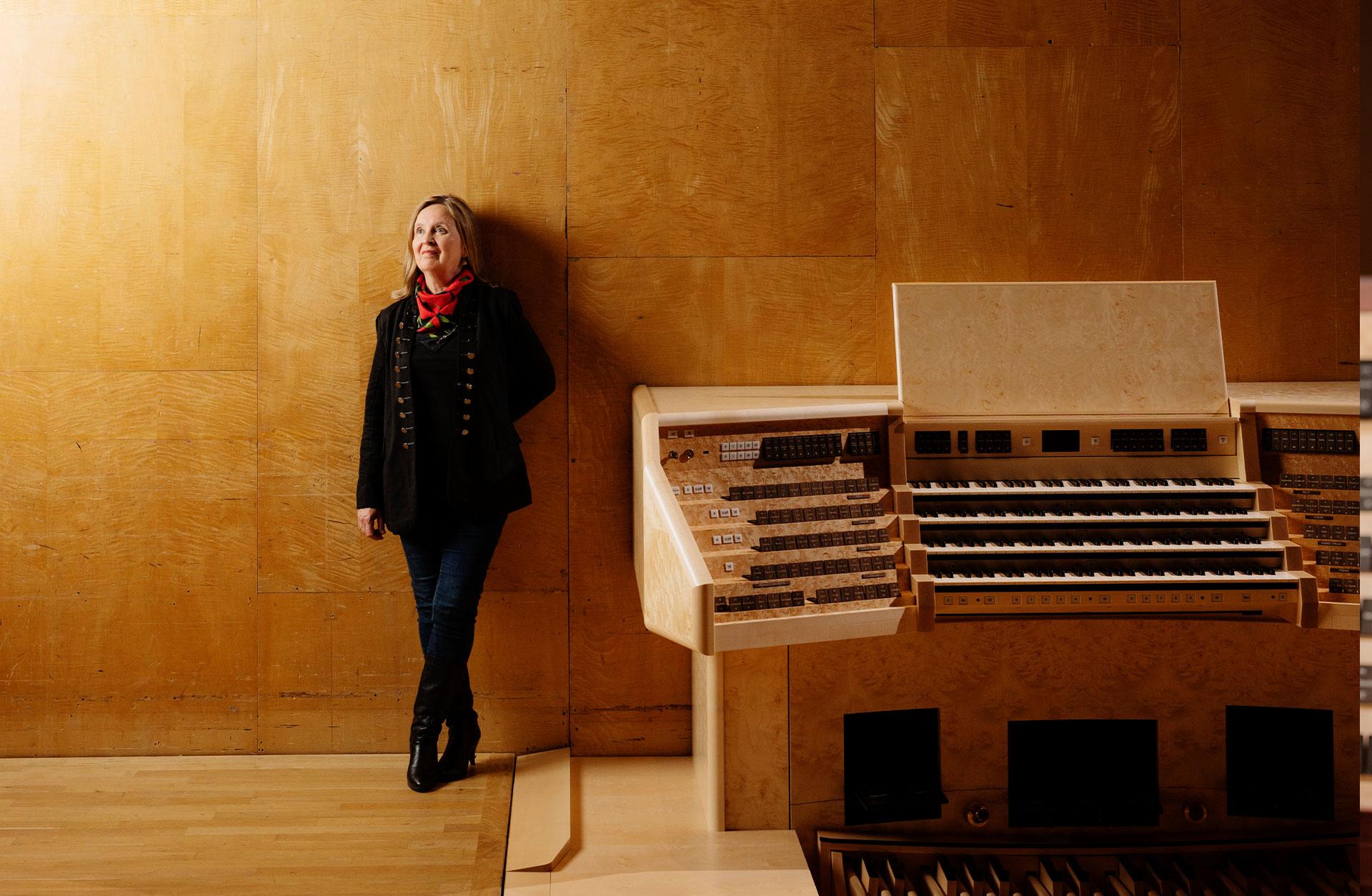 Karin Nelson står mot podiets bakre vägg med orgelns spelbord i förgrunden.