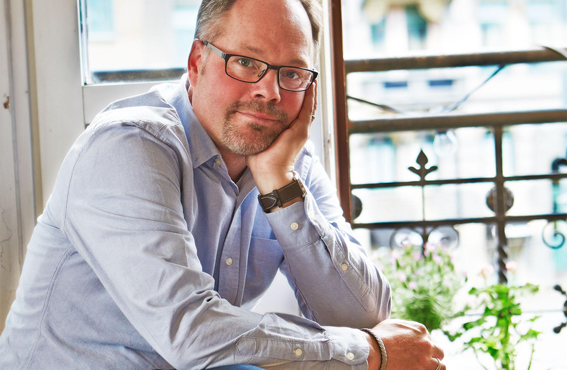Sittande man i skjorta och glasögon