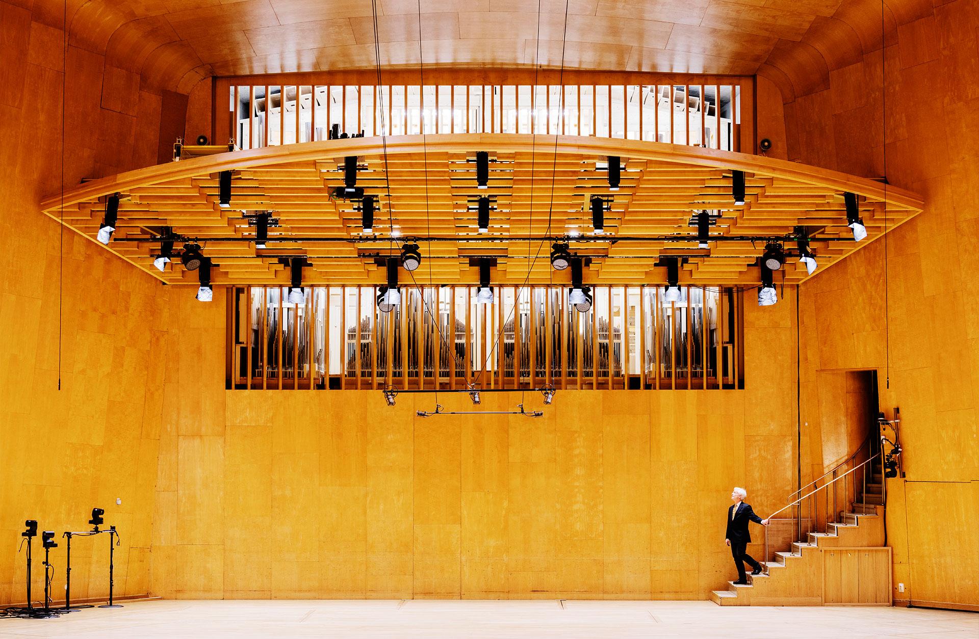 Hams Davidsson står på Podiet och tittar upp mot orgelluckorna. Han ser väldigt liten ut.