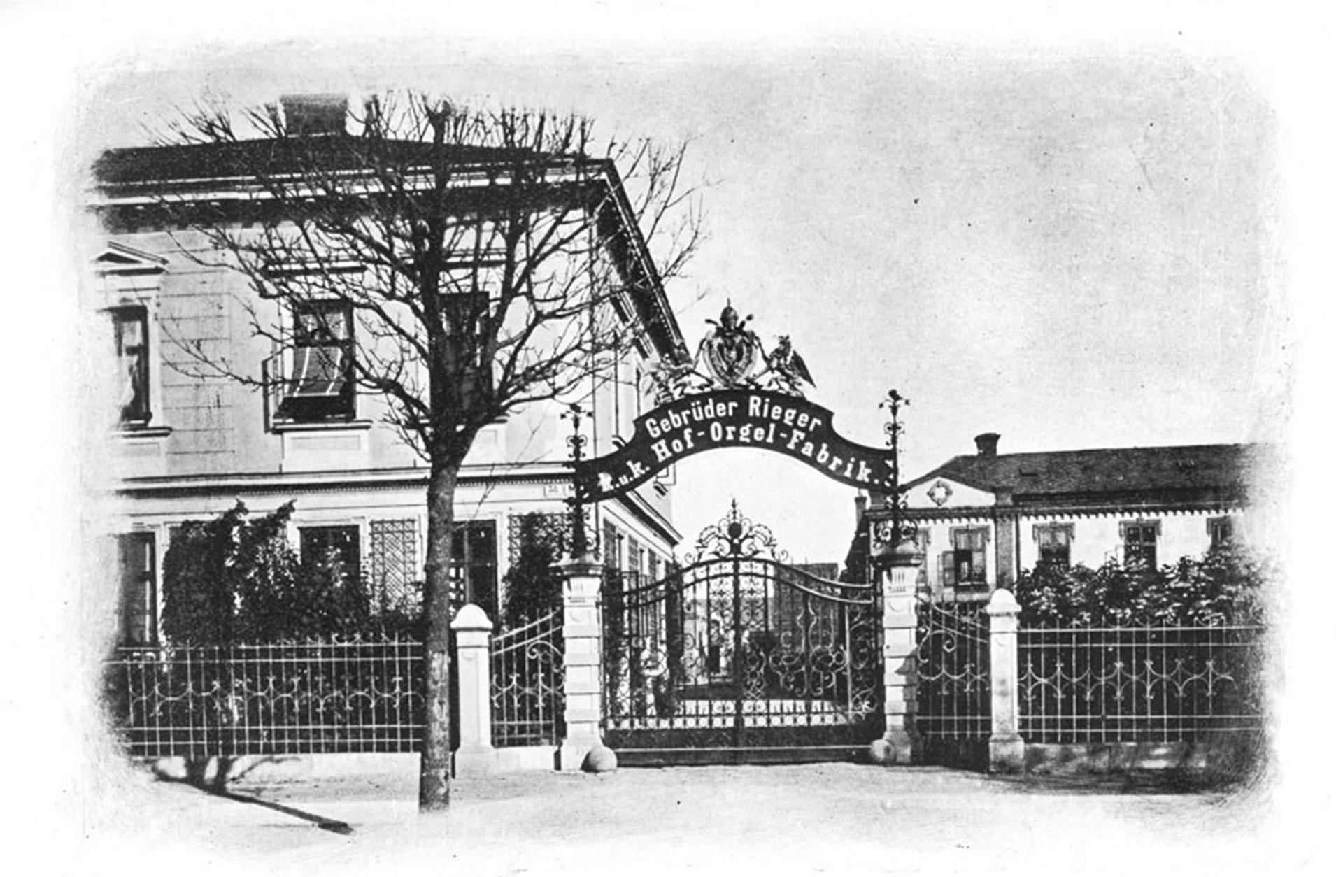 Svartvitt gammalt foto på entrégrinden till orgelfabriken.