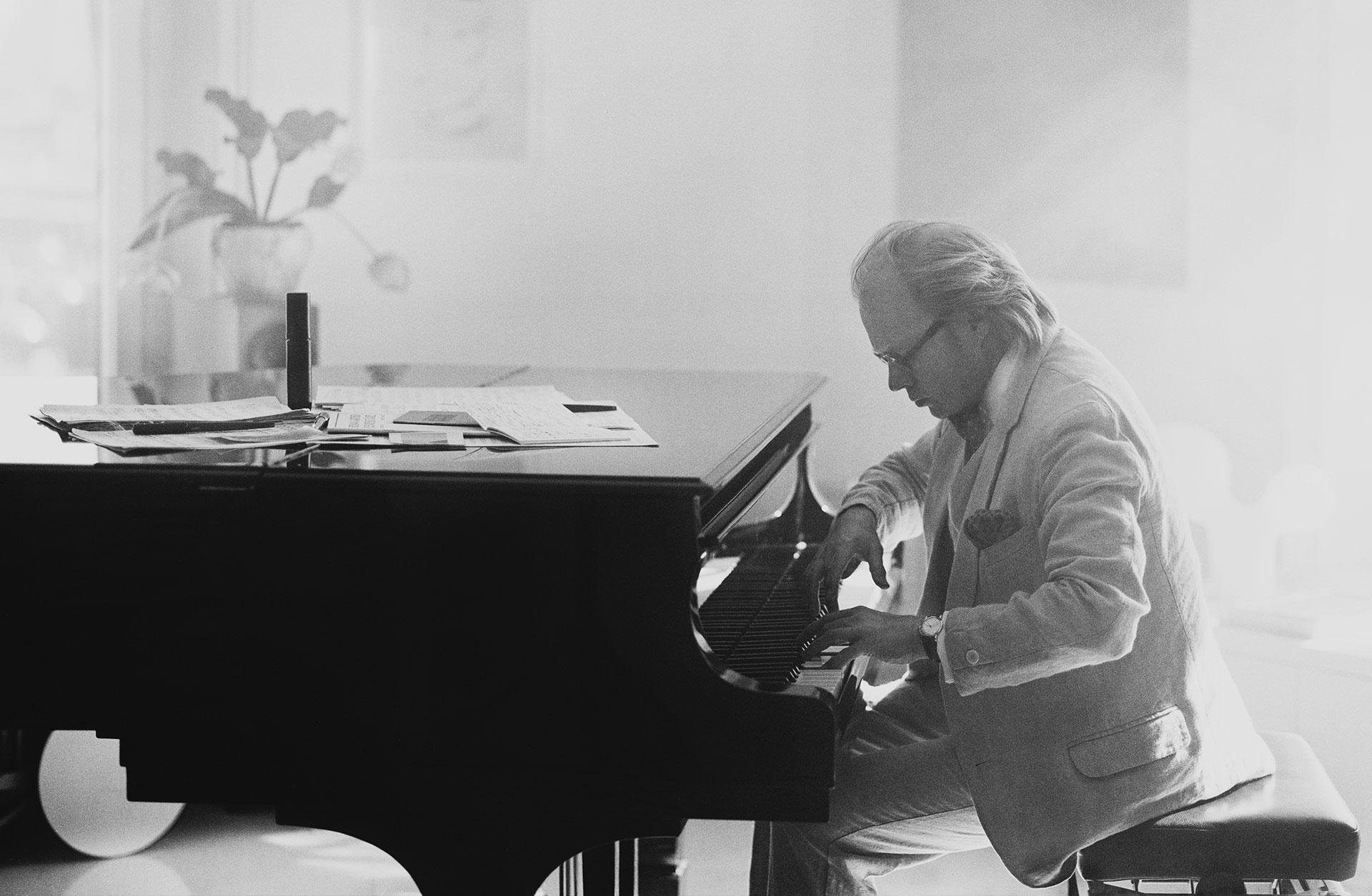 En svartvit bild med Roland Pöntien vid pianot
