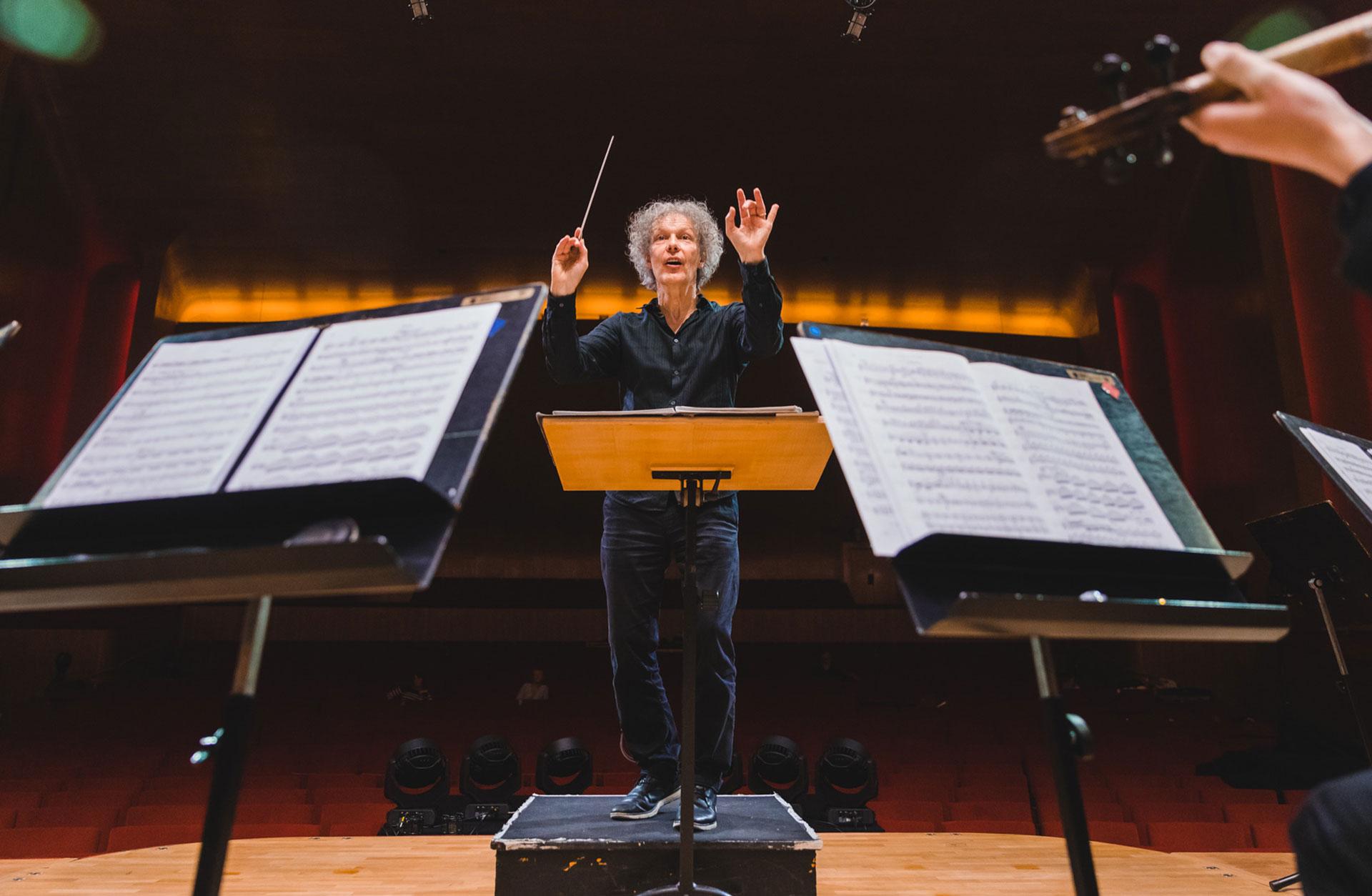 Simon Kim Phipps står på pulten och dirigerar