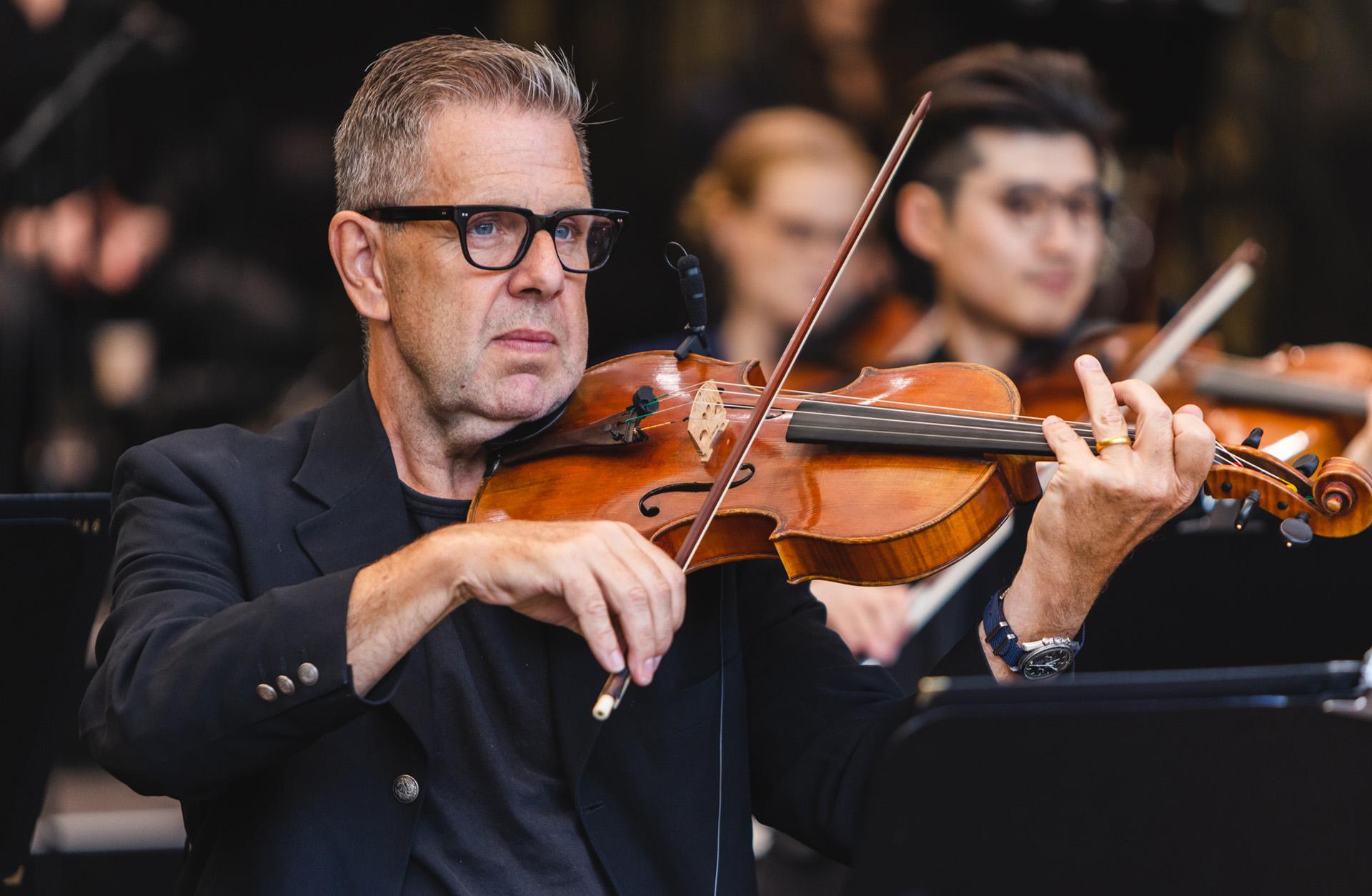 Man med glasögon spelar violin