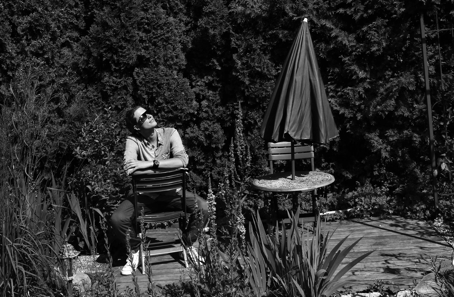 Ludwig Göransson sitter på en trädgårdsstol. Han har solglasögon och vänder sitt ansikte mot solen.